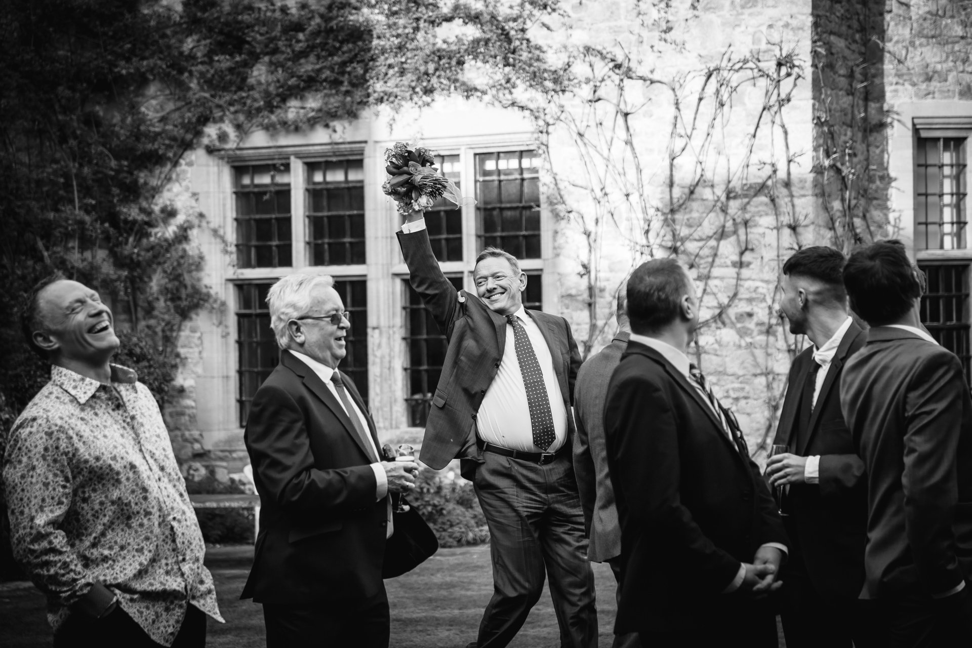 Male guest catches bouquet in the Courtyard at Allington Castle