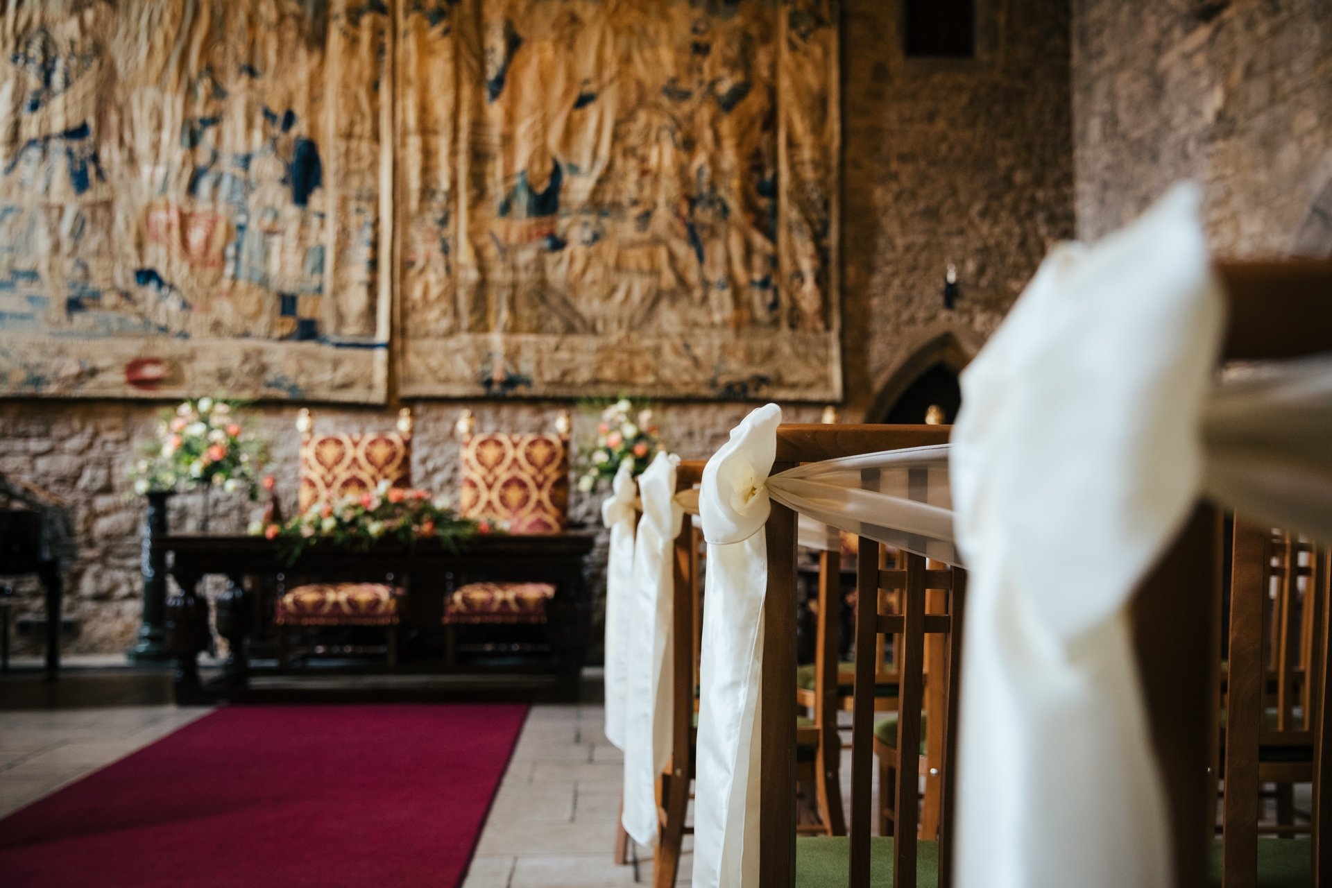 Cream sashes decorating the chairs in the medieval Castle of Allington, Kent Wedding Venue