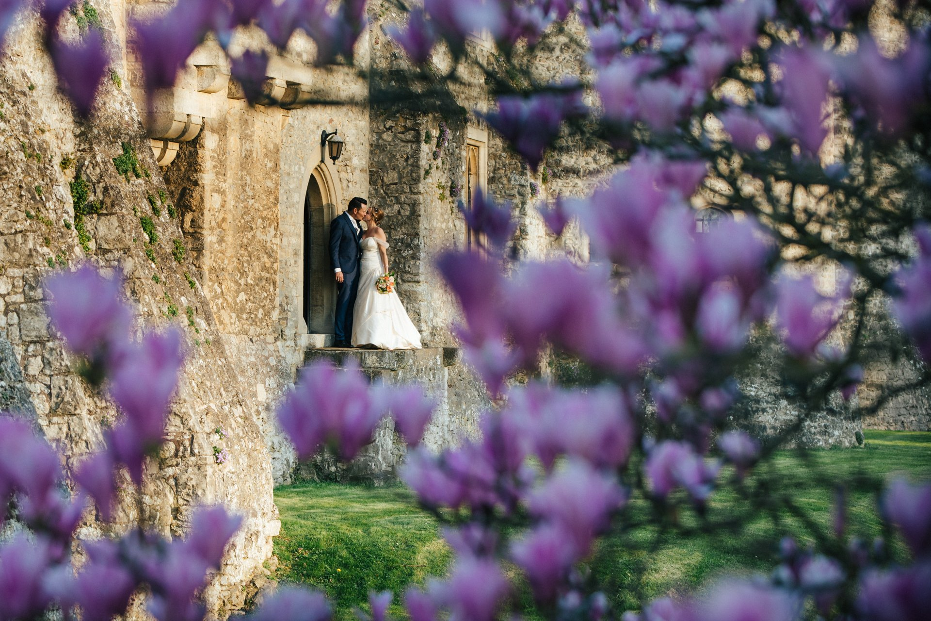 Bride and Groom embracing through the magnolia at Allington Castle