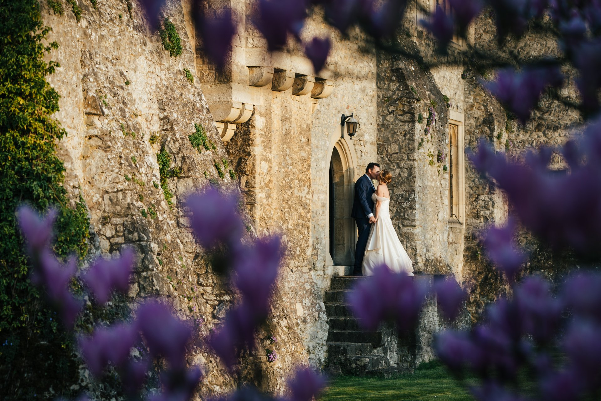 Bride and groom kissing through the magnolia at Allington Castle