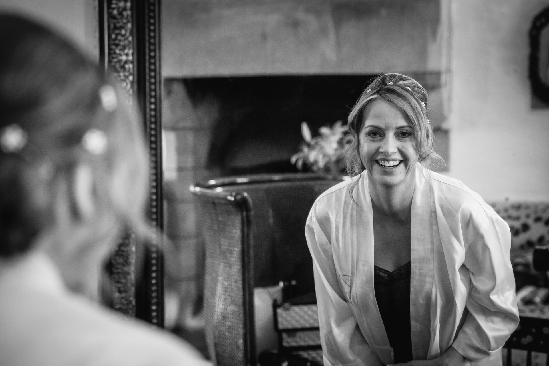 Smiling Bride as she looks at her reflection on a mirror getting ready for her Wedding at Allington Castle, Kent