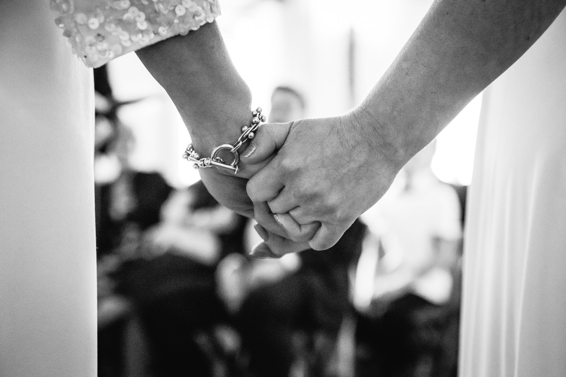 Two brides holding hands during their wedding ceremony