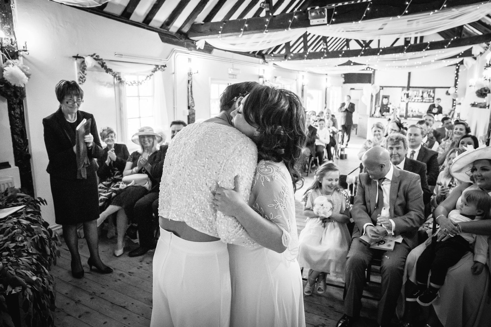 First hug during the ceremony of two brides at The Bull Hotel, Kent