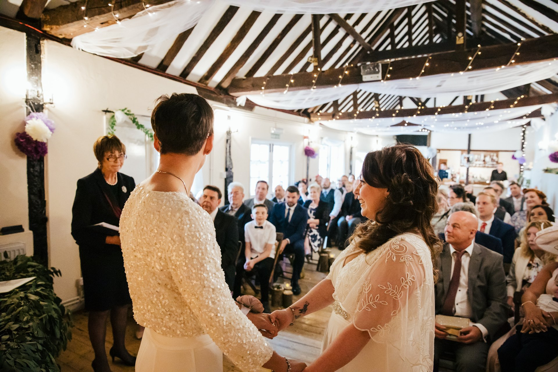 Two Brides holding hands together infant of their guests in their wedding ceremony at The Bull Hotel, Kent