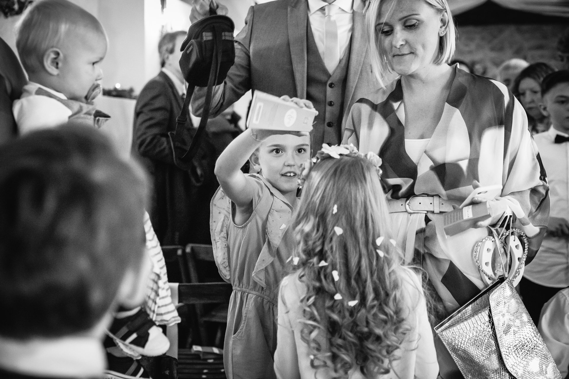 Child pouring confetti over another Childs head after a wedding ceremony