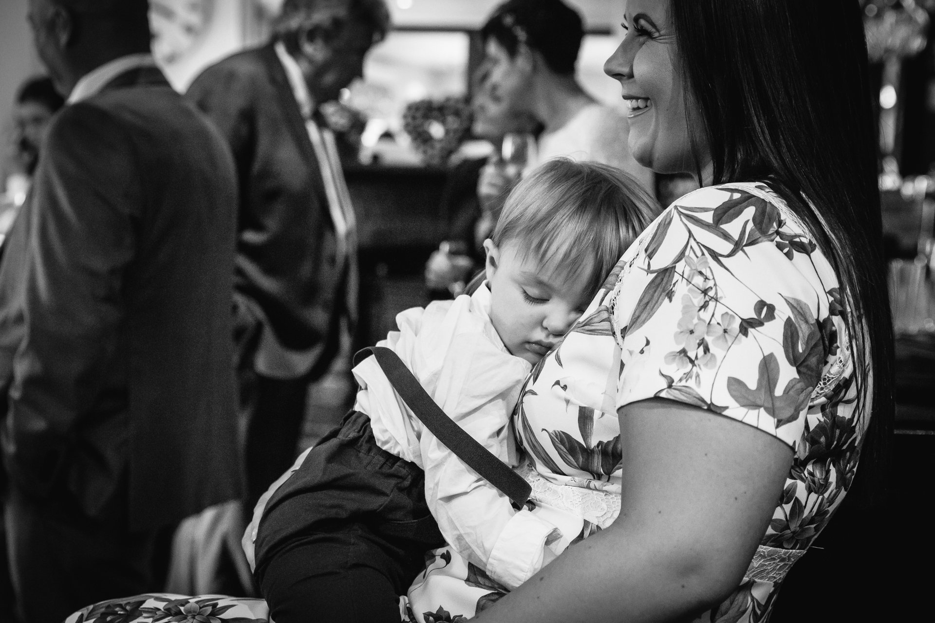 Baby asleep on his mum during wedding ceremony