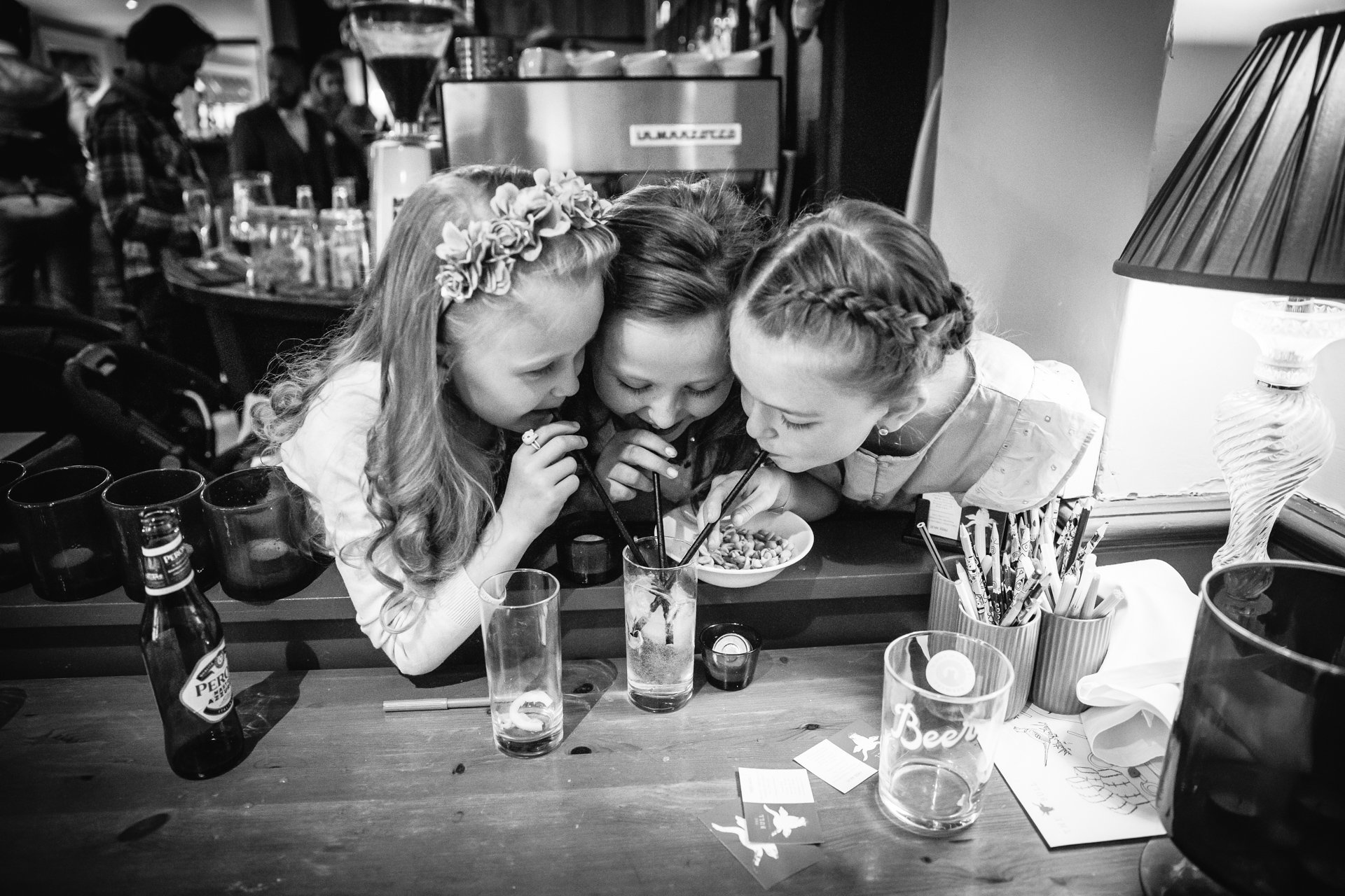Three girls blowing bubbles into their drink at Wedding reception