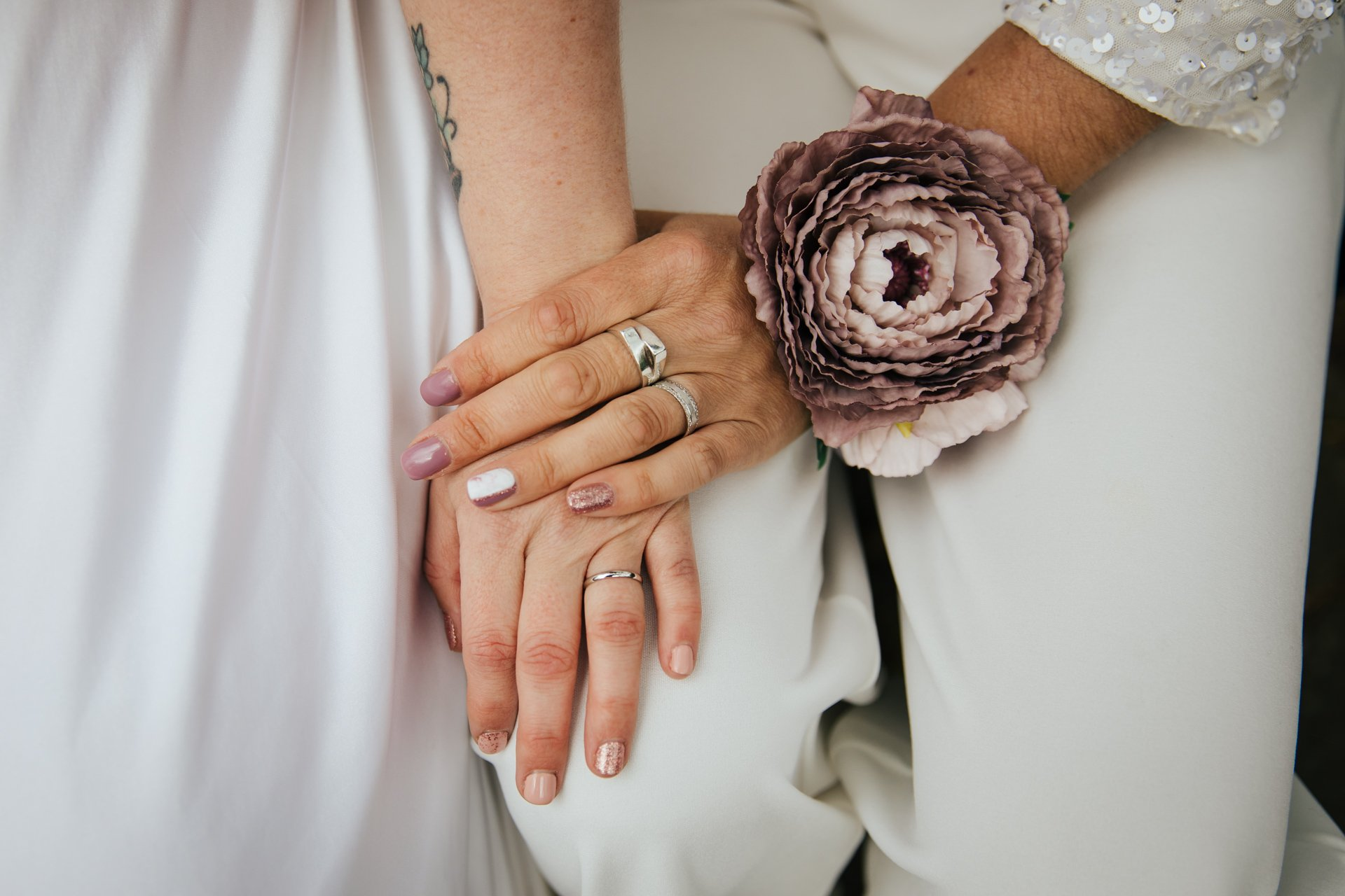 Hands of two brides with ring and beautiful dusky pink wrist corsage