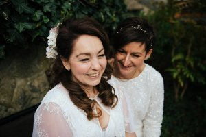 Brides laughing during their wedding portraits