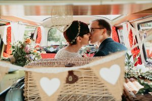 Couple kissing in the back of a VW camper after their wedding