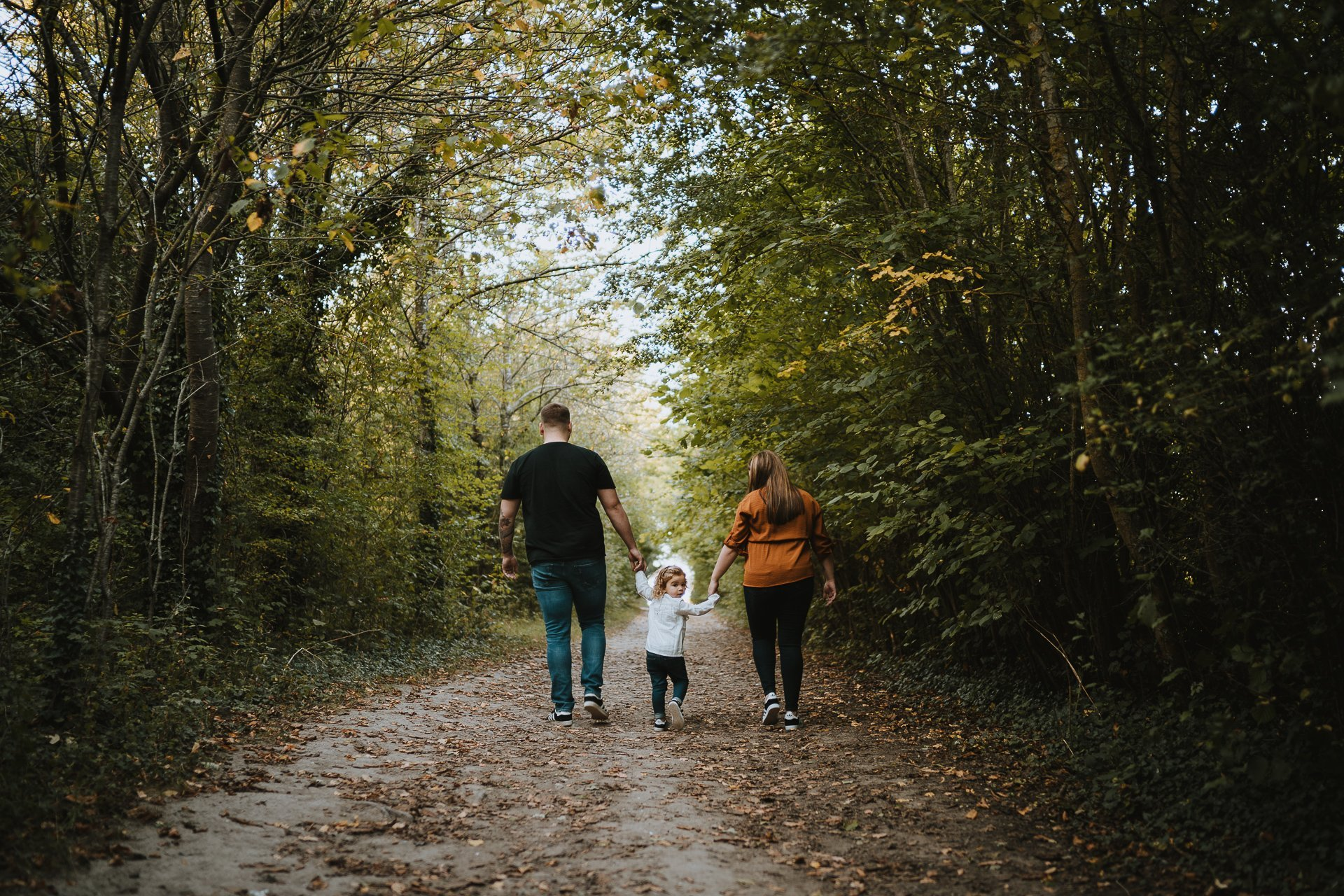 Engaged couple and their daughter walking through woodland at Lullingstone Country Park Kent