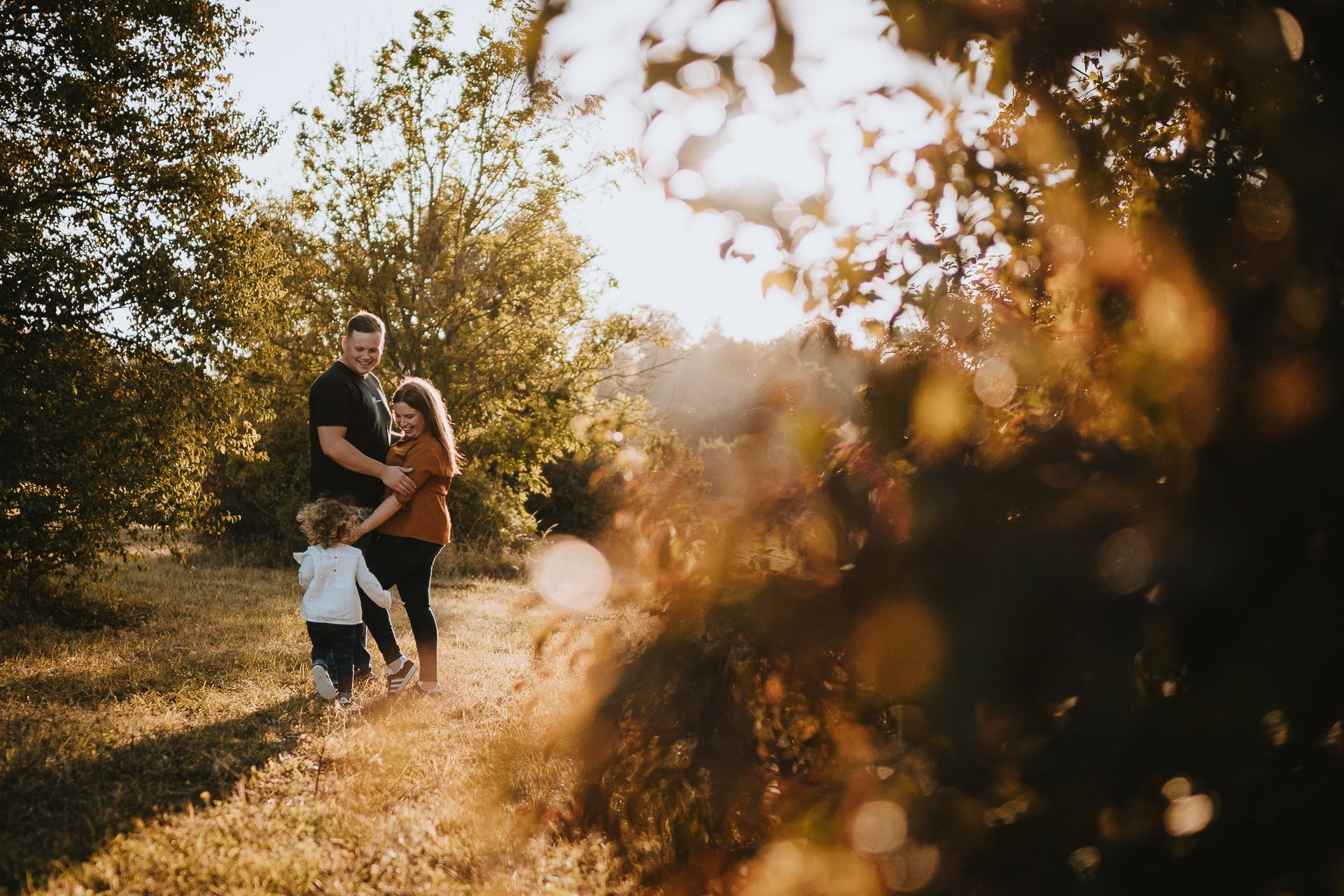 Engaged couple and their daughter in warm autumn evening light at Lullingstone Country Park Kent