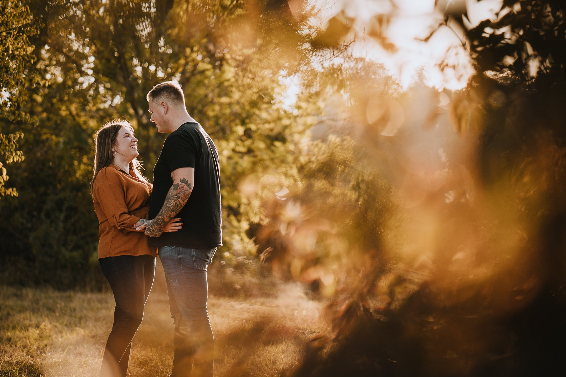 Engaged couple holding hands in autumn woodland