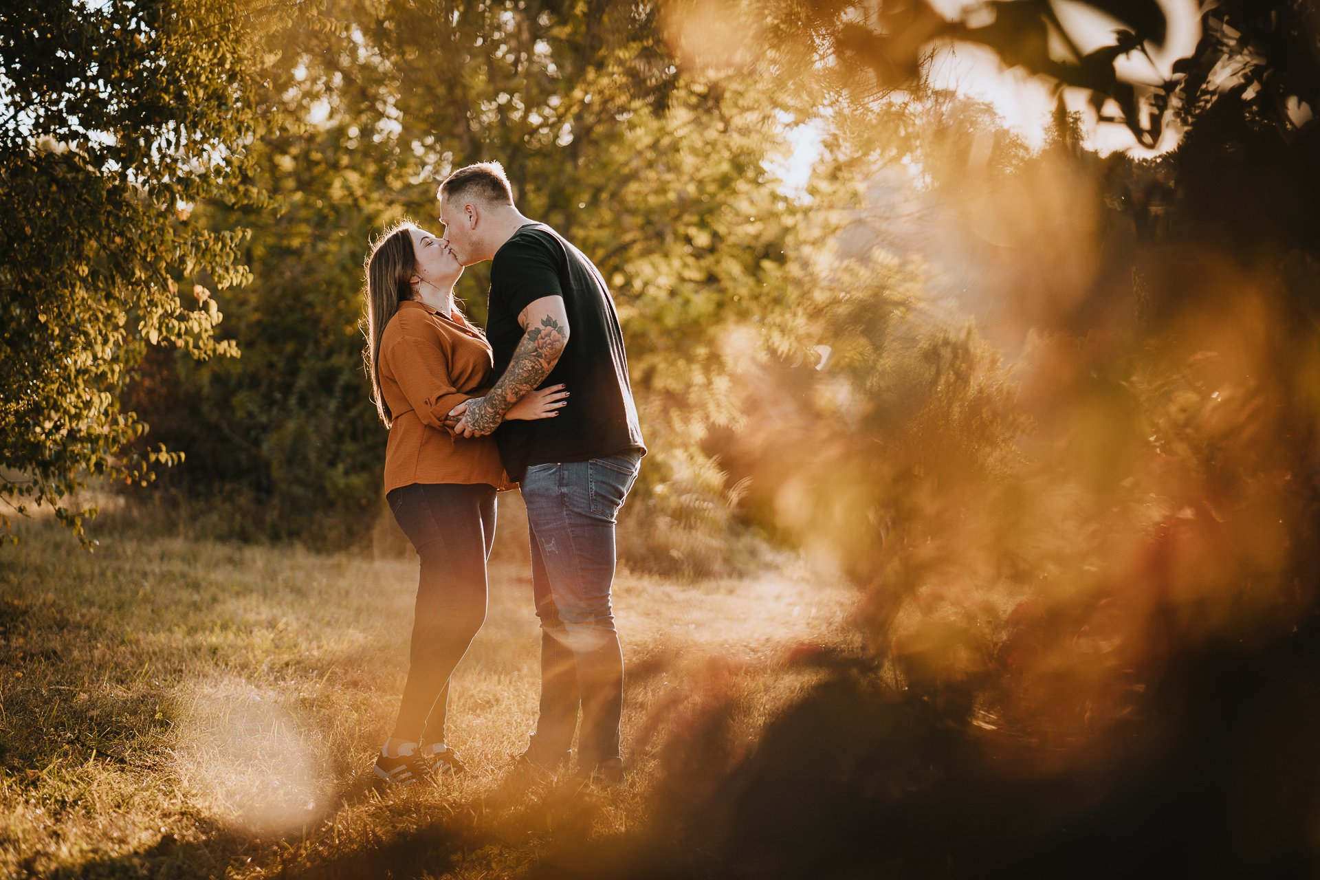 Engaged couple kissing during their autumnal sunset engagement shoot at Lullingstone Country Park, Kent
