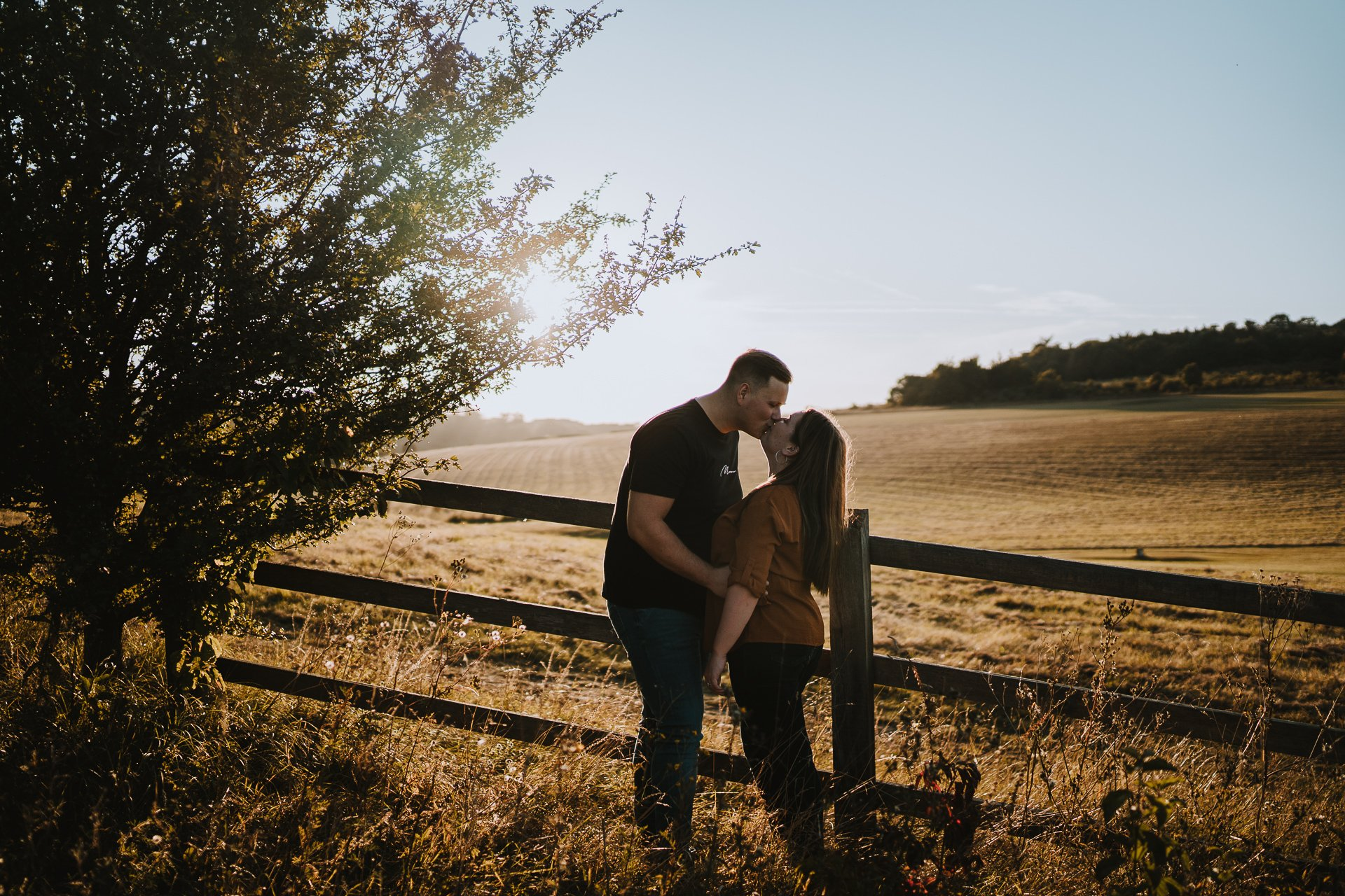 Engaged couple looking at each other during their autumnal sunset engagement shoot at Lullingstone Country Park, Kent