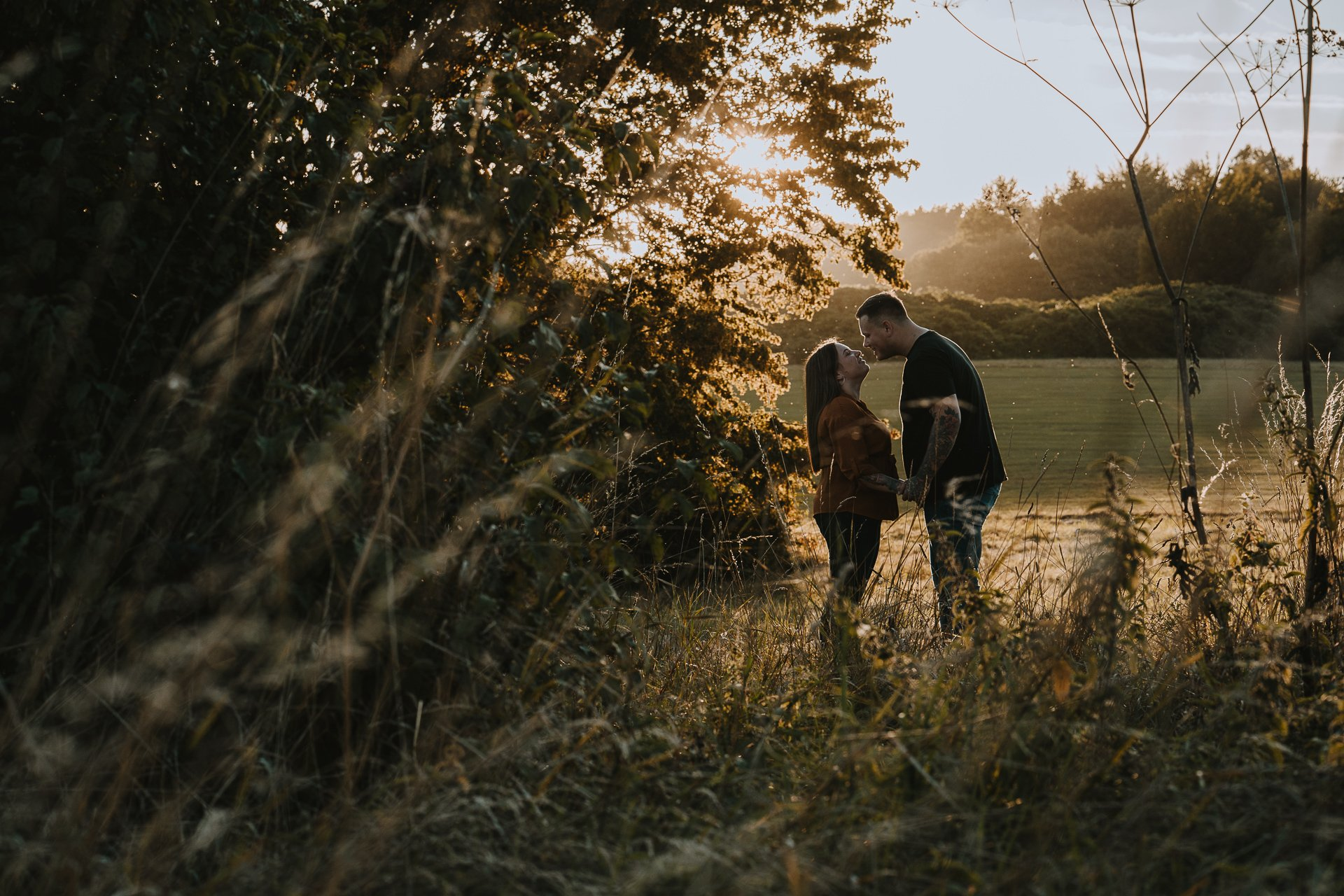 Engaged couple looking at each other during their golden hour couple shoot at Lullingstone Country Park, Kent