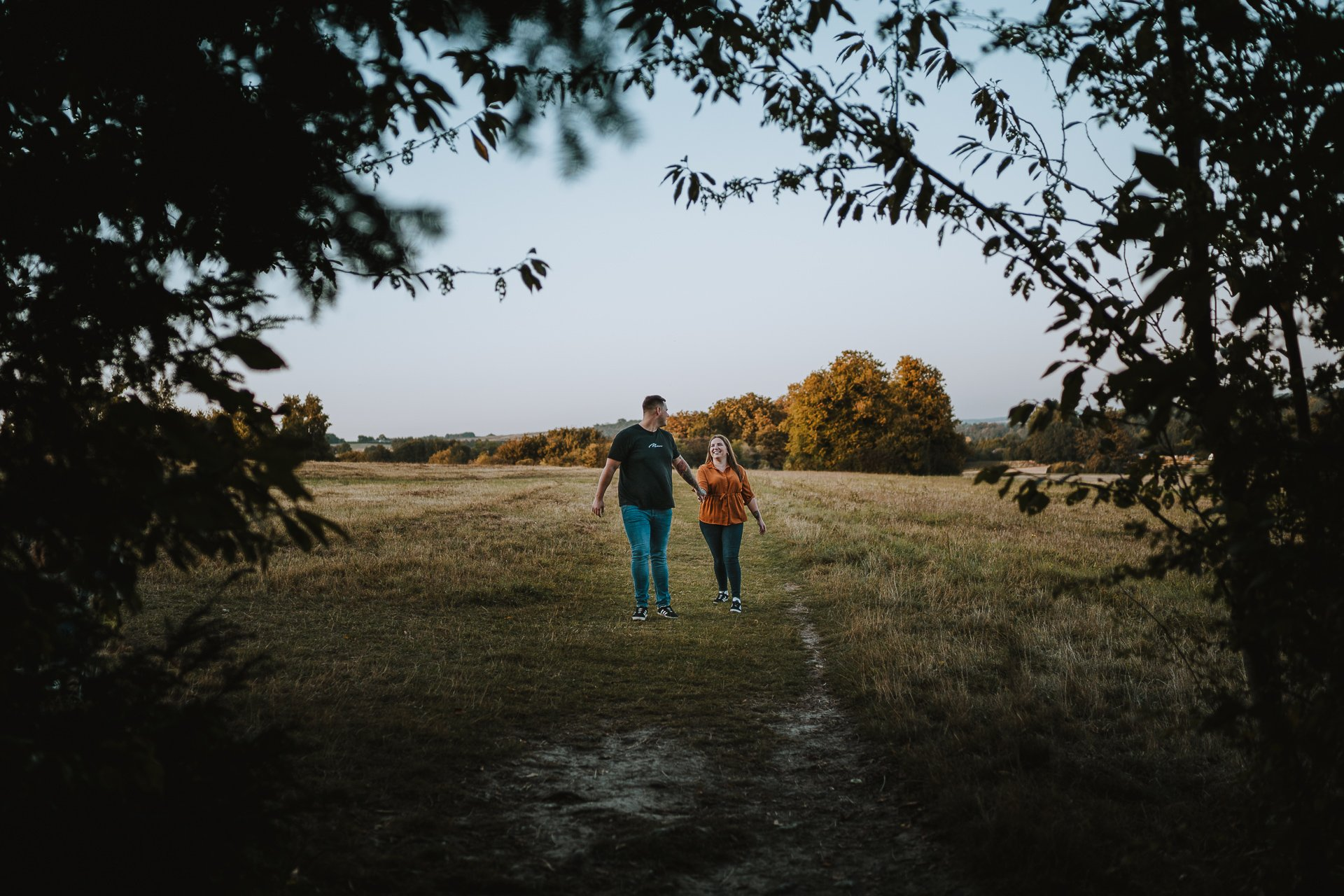 Engaged couple walking and smiling at each other in their pre wedding shoot at Lullingstone Country Park, Kent