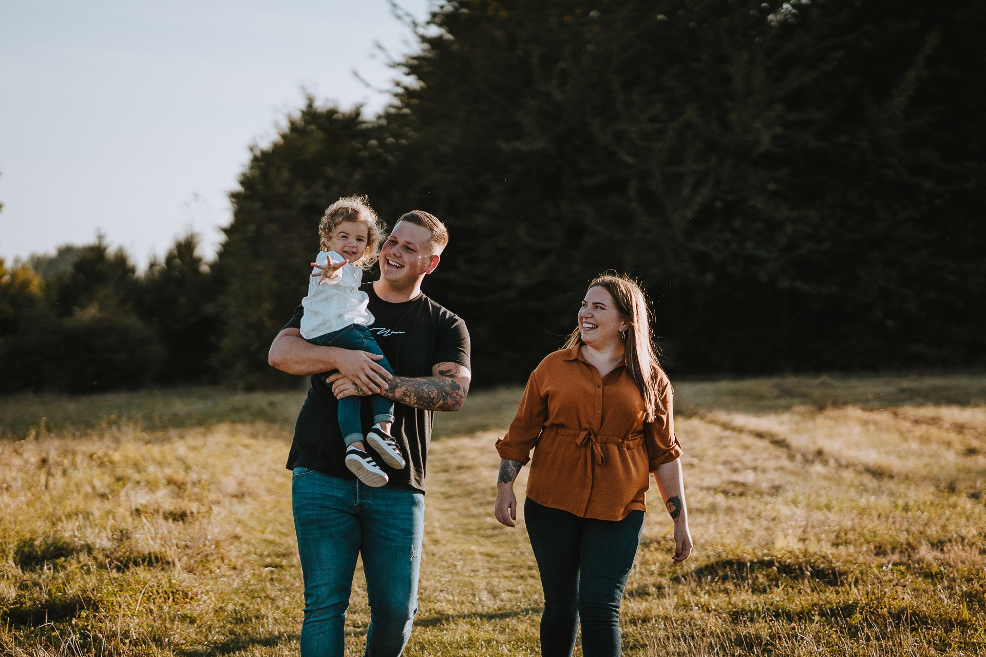 Engaged couple and their daughter walking in warm evening light at Lullingstone Country Park Kent