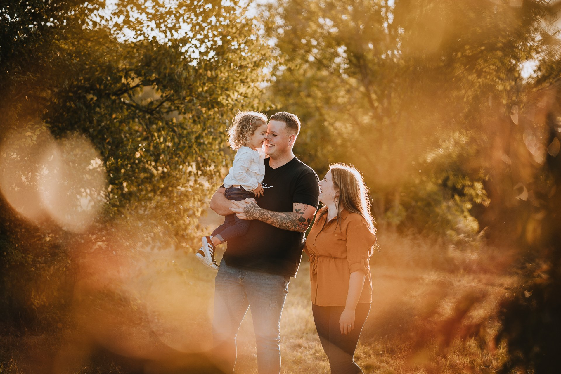 Family laughing in warm autumn evening light at Lullingstone Country Park Kent