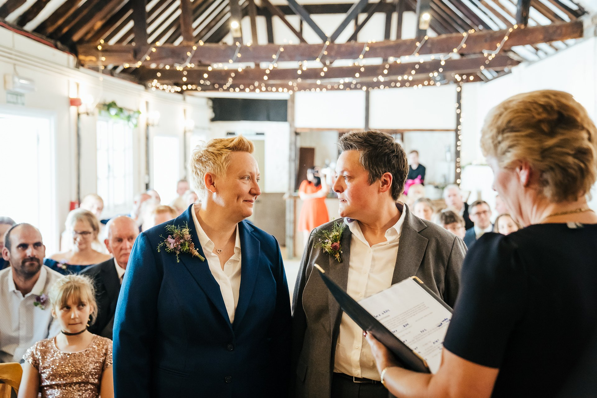 Two brides exchange loving looks during their Kent ceremony