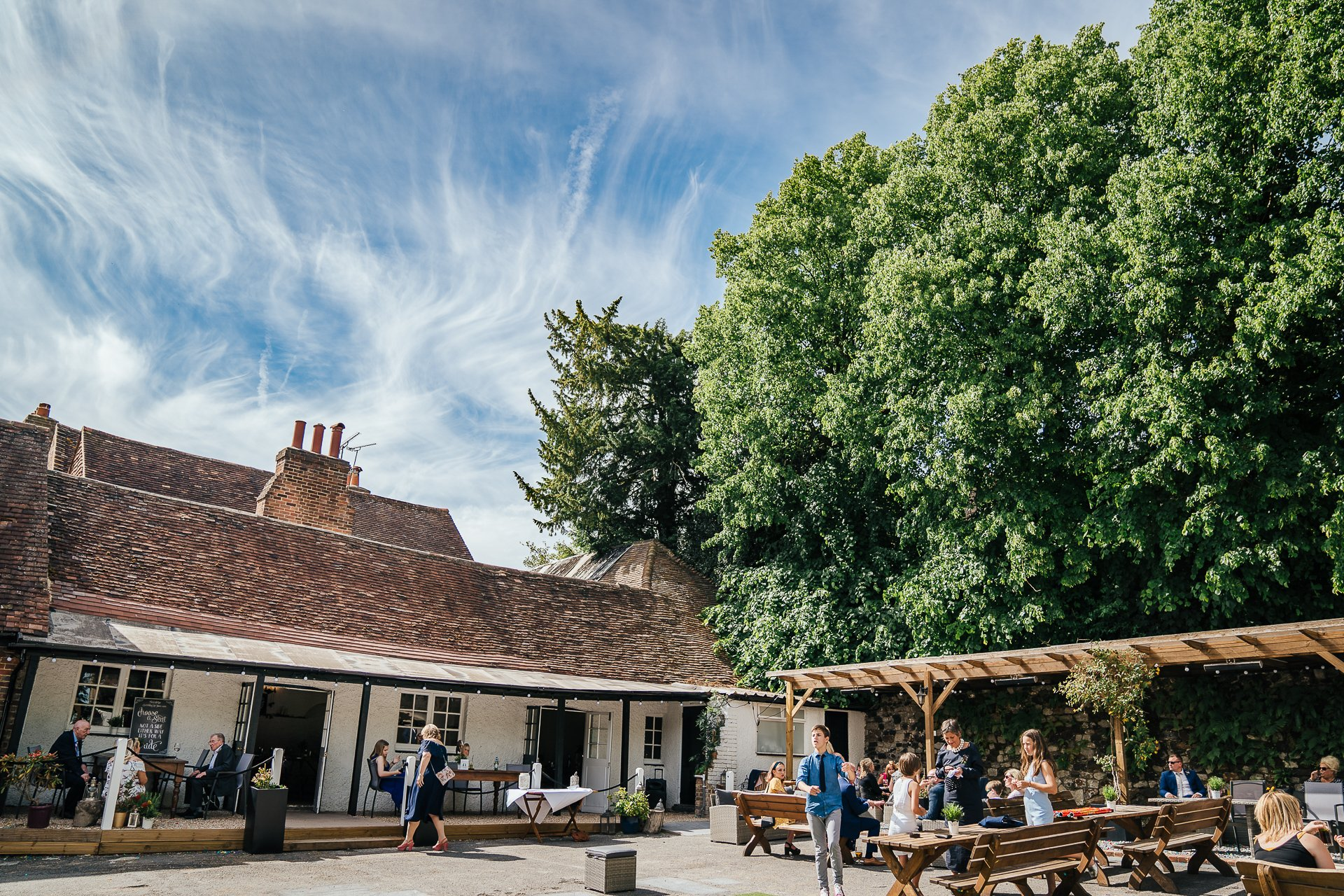 The Courtyard at the Bull Hotel Kent with wedding guests and blue sky