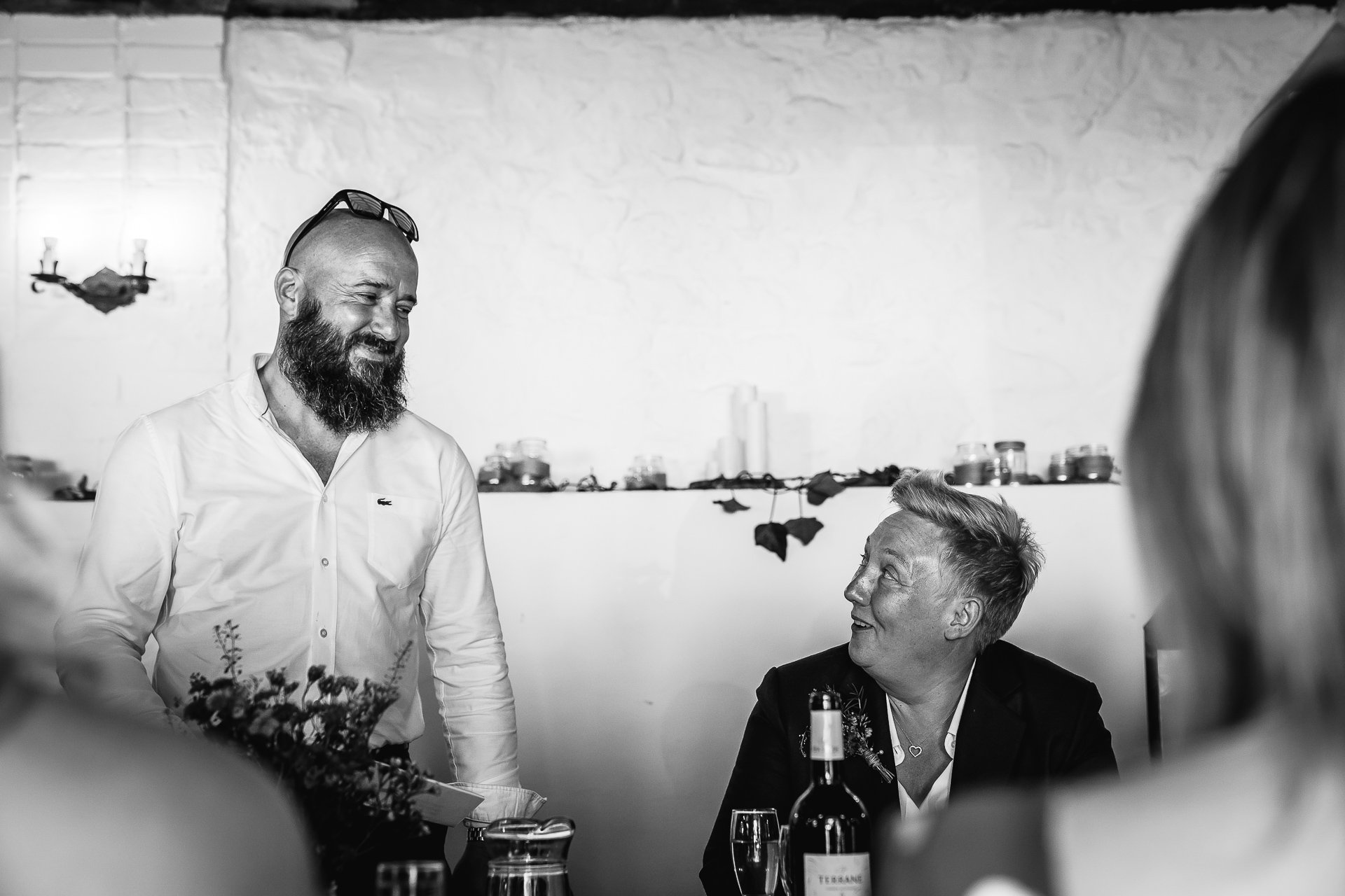 Best man and bride exchanging smiles during wedding speeches