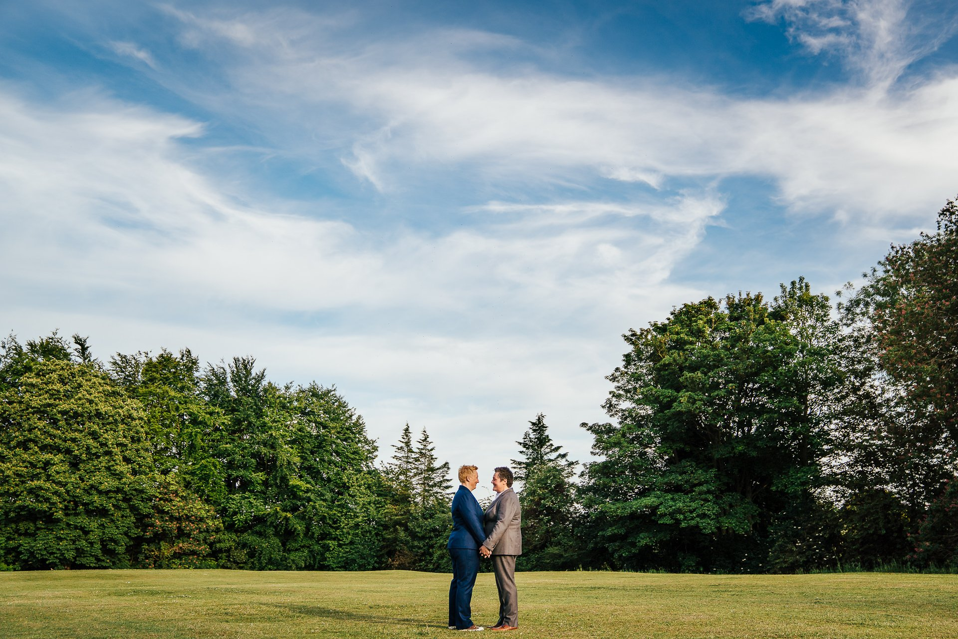Two brides embracing in a field under blue sky