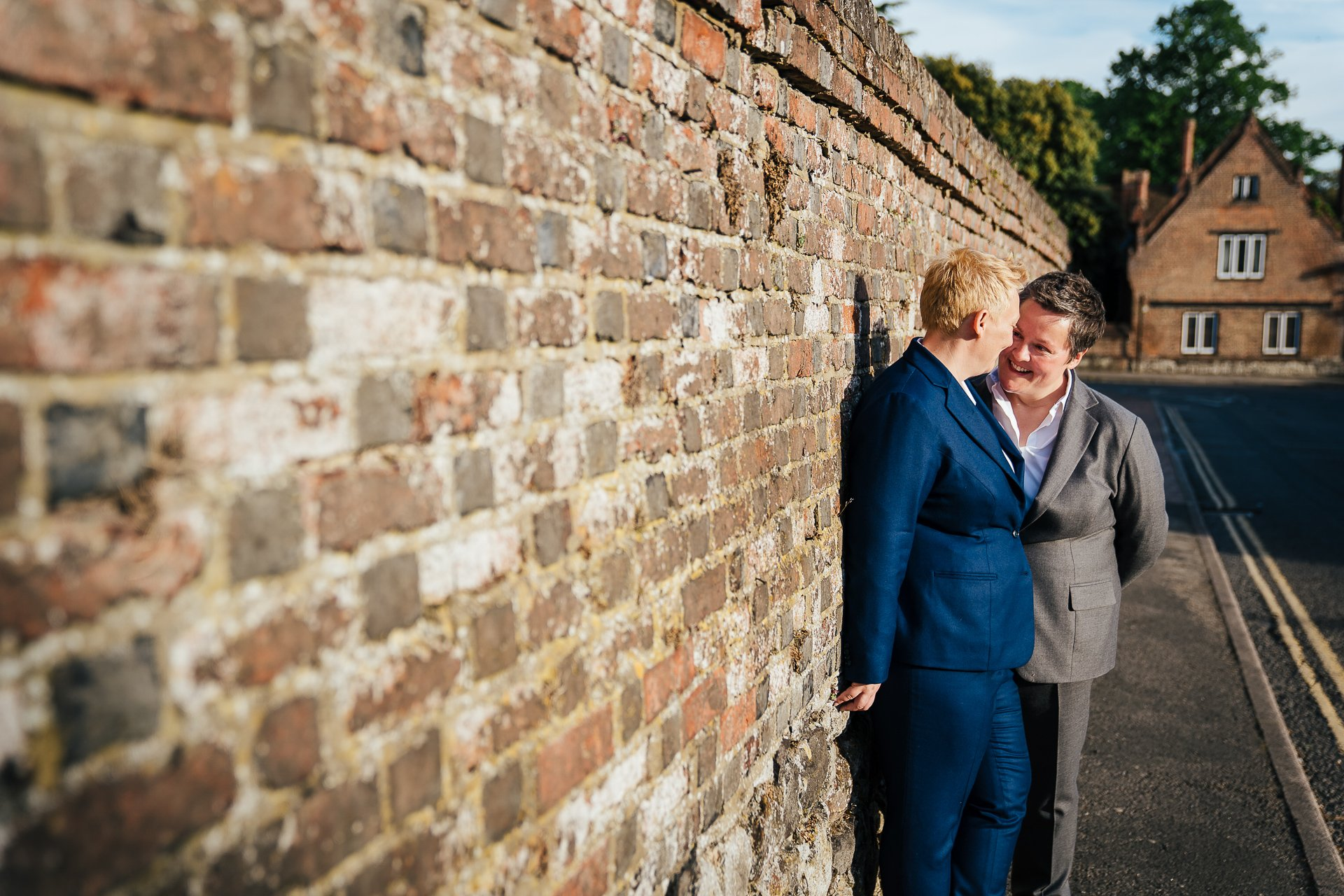 Couple embracing against wall after their wedding ceremony