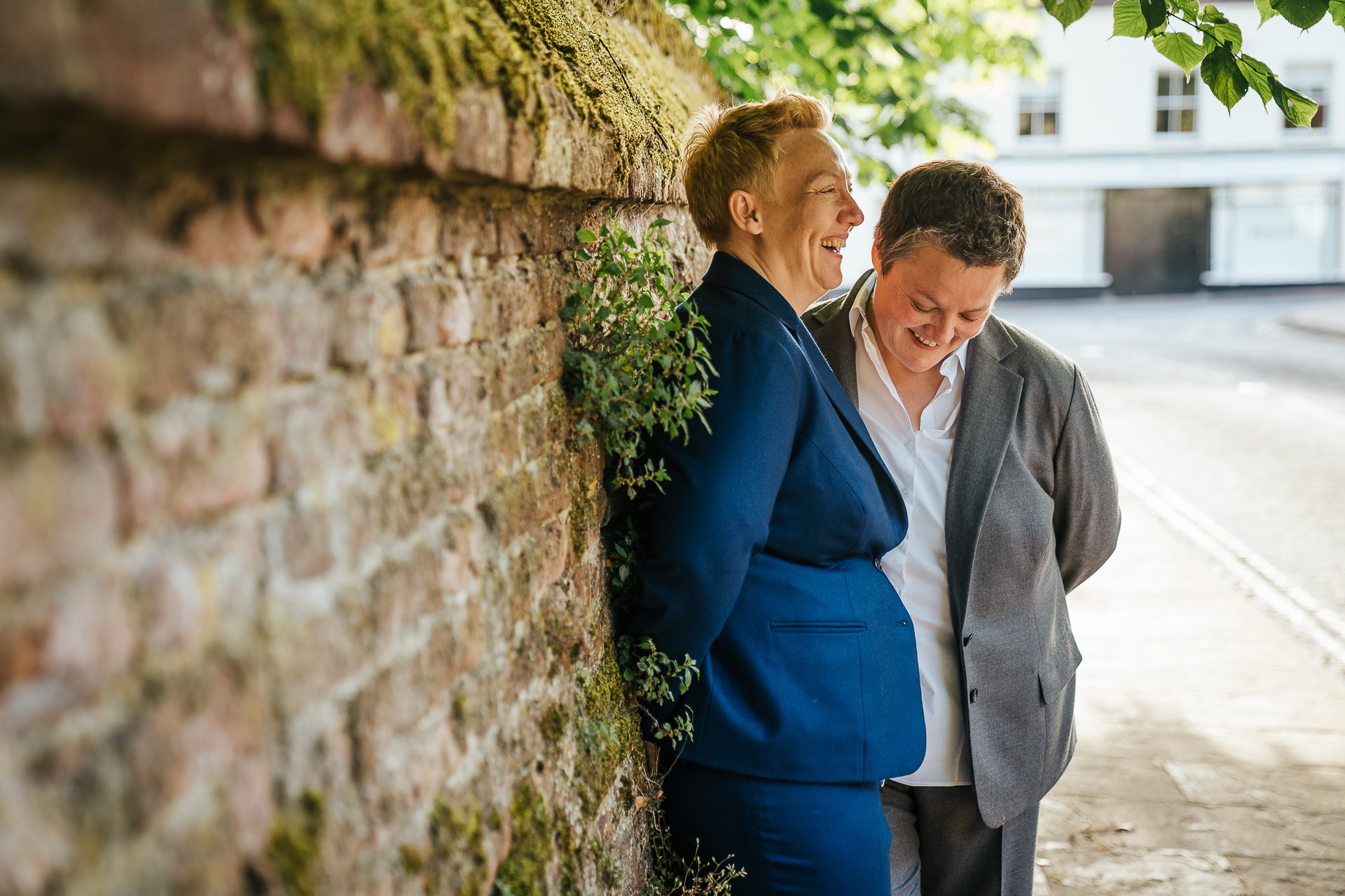 Couple laughing together against wall after their wedding ceremony