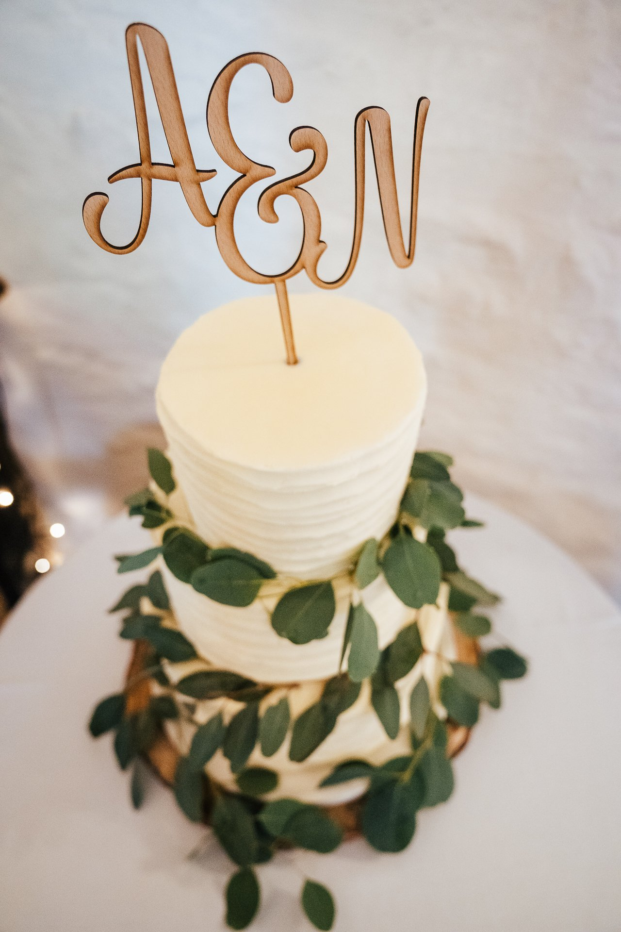 Simple cream butter cream decorated wedding cake with A & N cake topper
