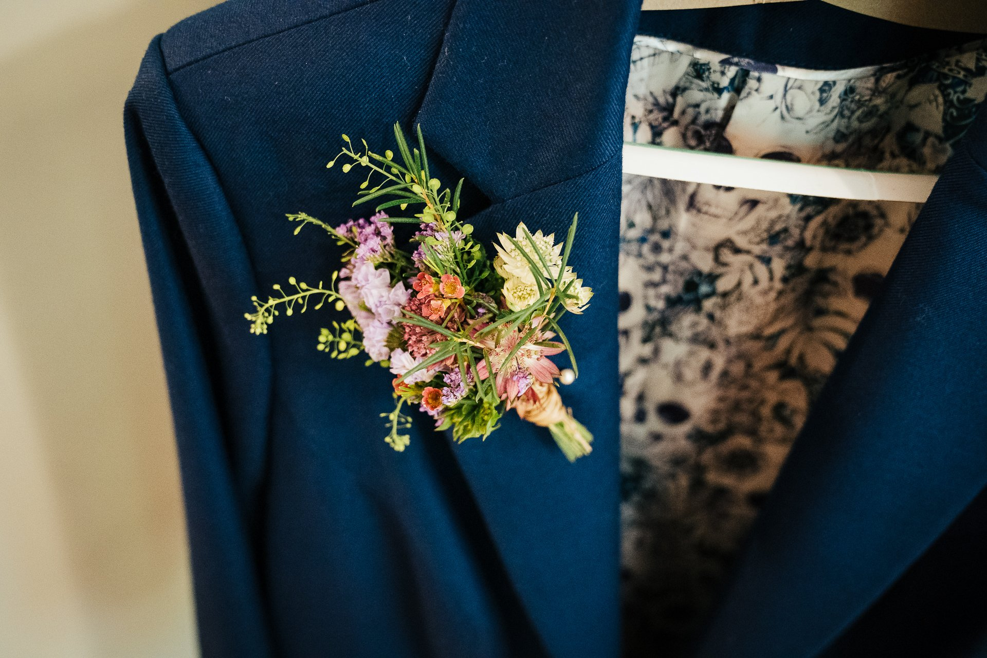 gorgeous button hole flowers on brides navy suit
