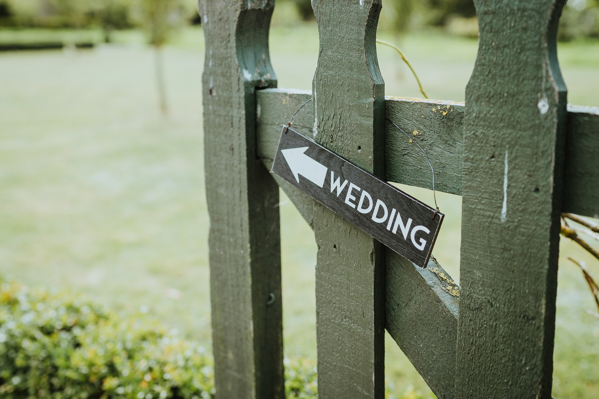 Wedding this way sign on green garden gate