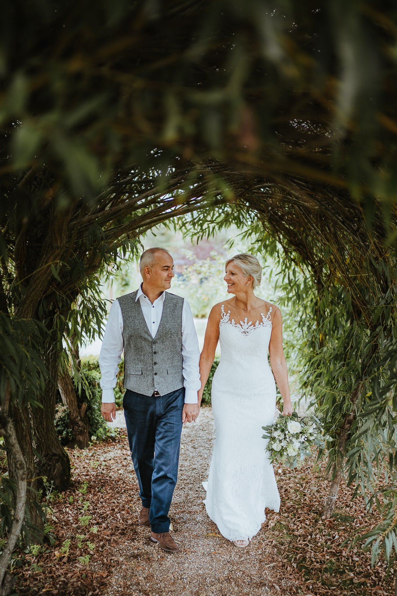 Married couple walk through willow arch holding hands