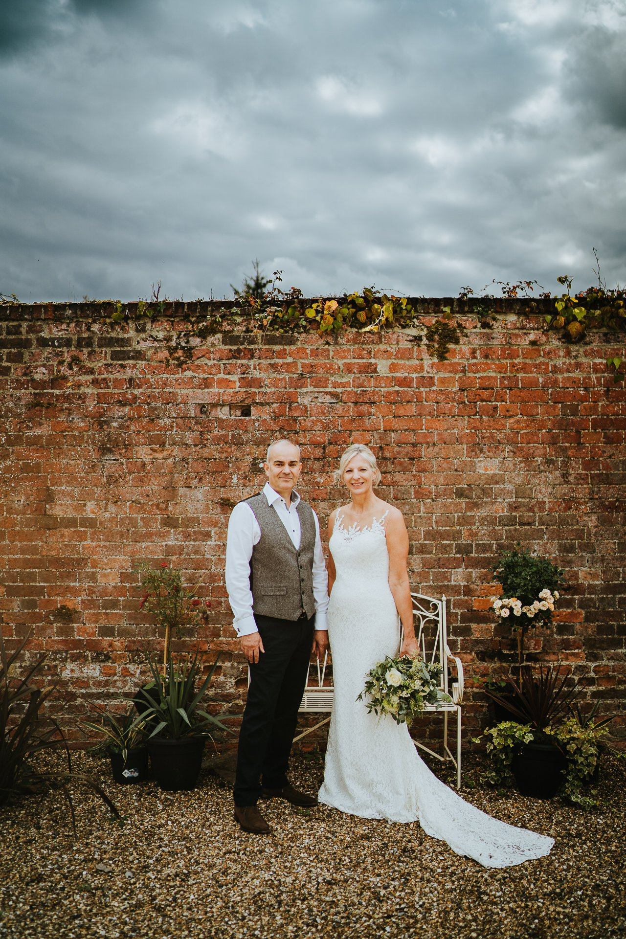 Bride and Groom infant of red brick wall at The Secret Garden