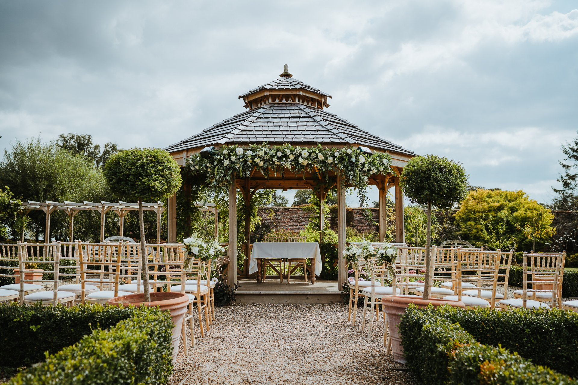 Wedding ceremony gazebo decorated in white and green flowers