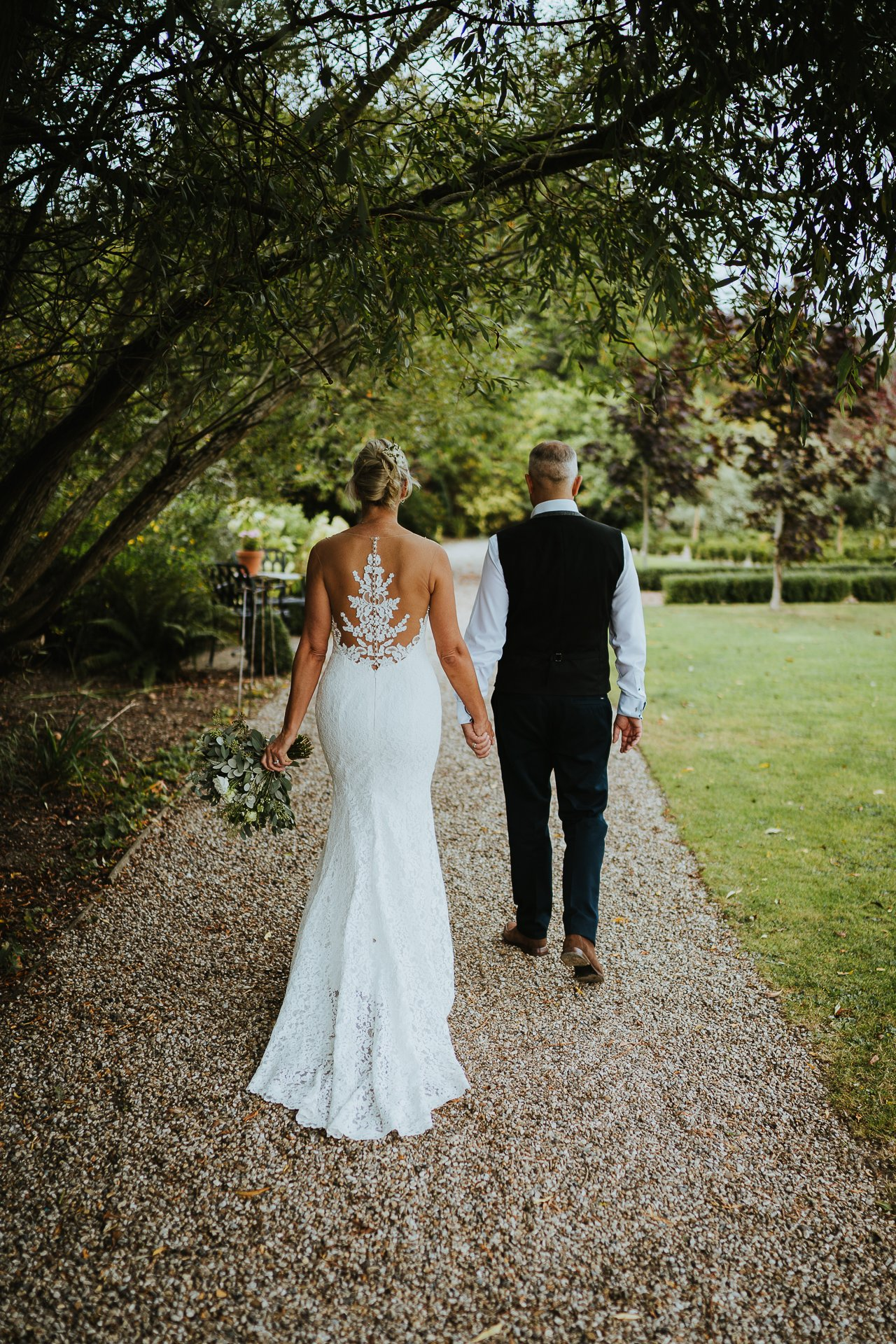 Bride and Groom holding hands and walking through the gardens