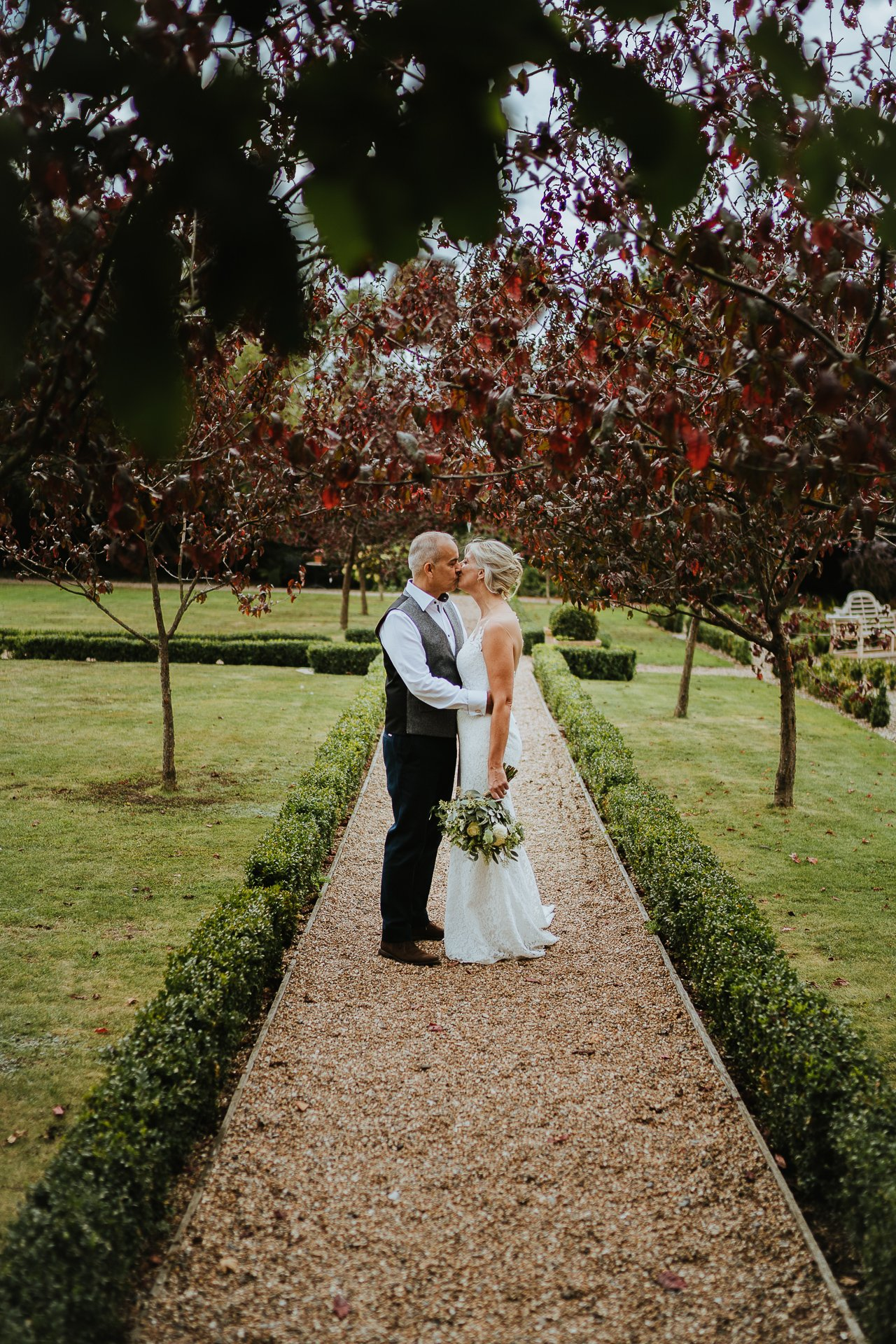 Groom holding and kissing his bride in the secret garden