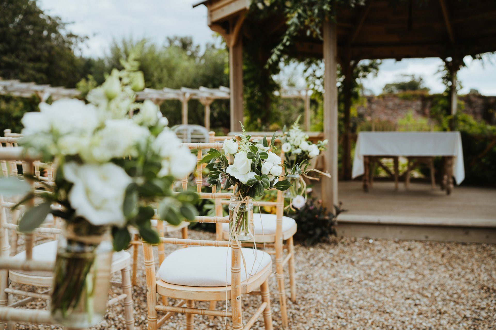 white roses and green foliage on the ceremony chairs at Secret Garden Kent