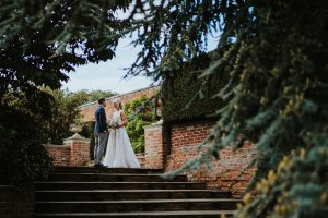 Couple smiling with each other and holding hands during portraits after their wedding at Braxted Park