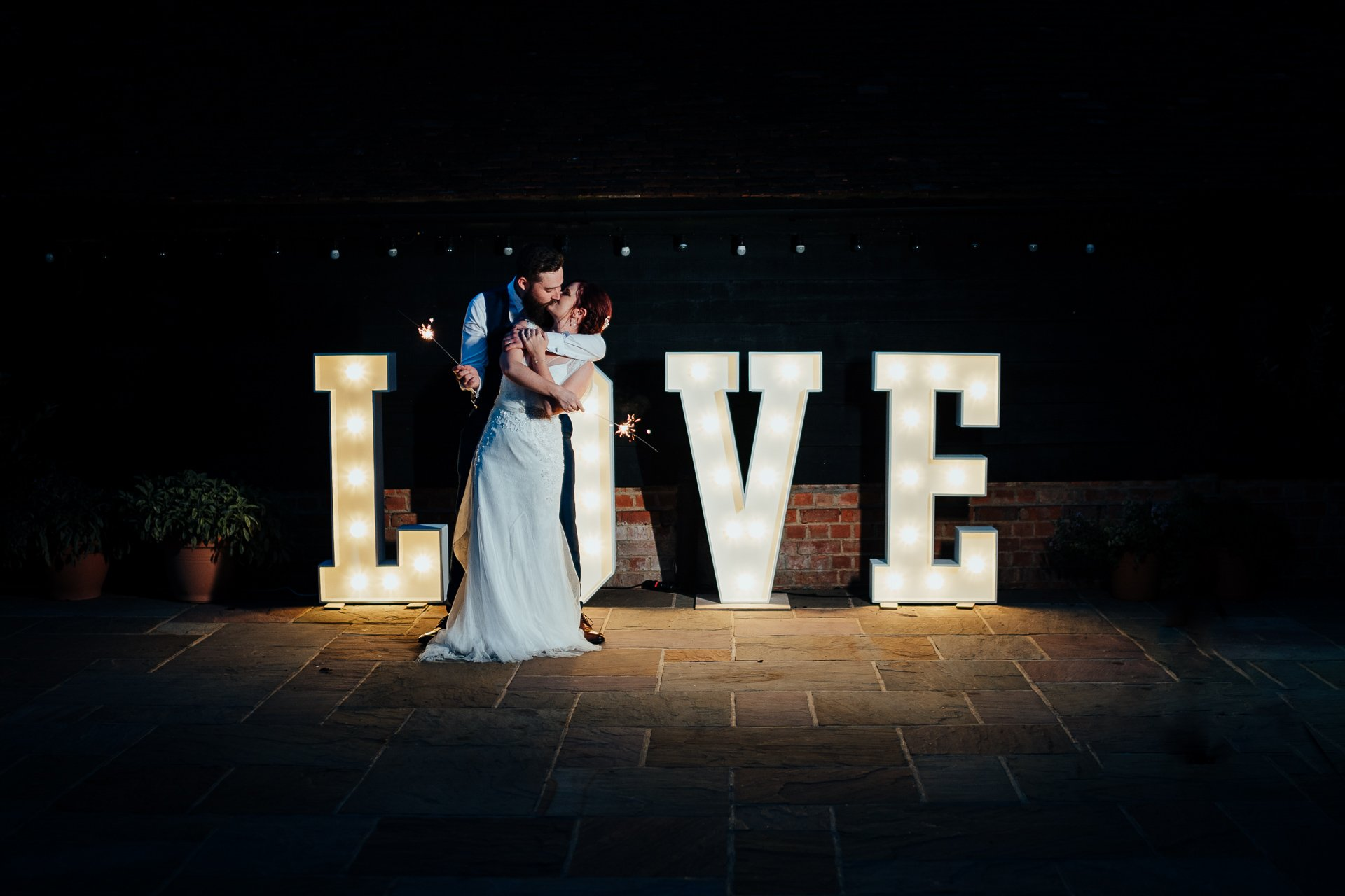 Bride and Groom kissing in front of LOVE sign