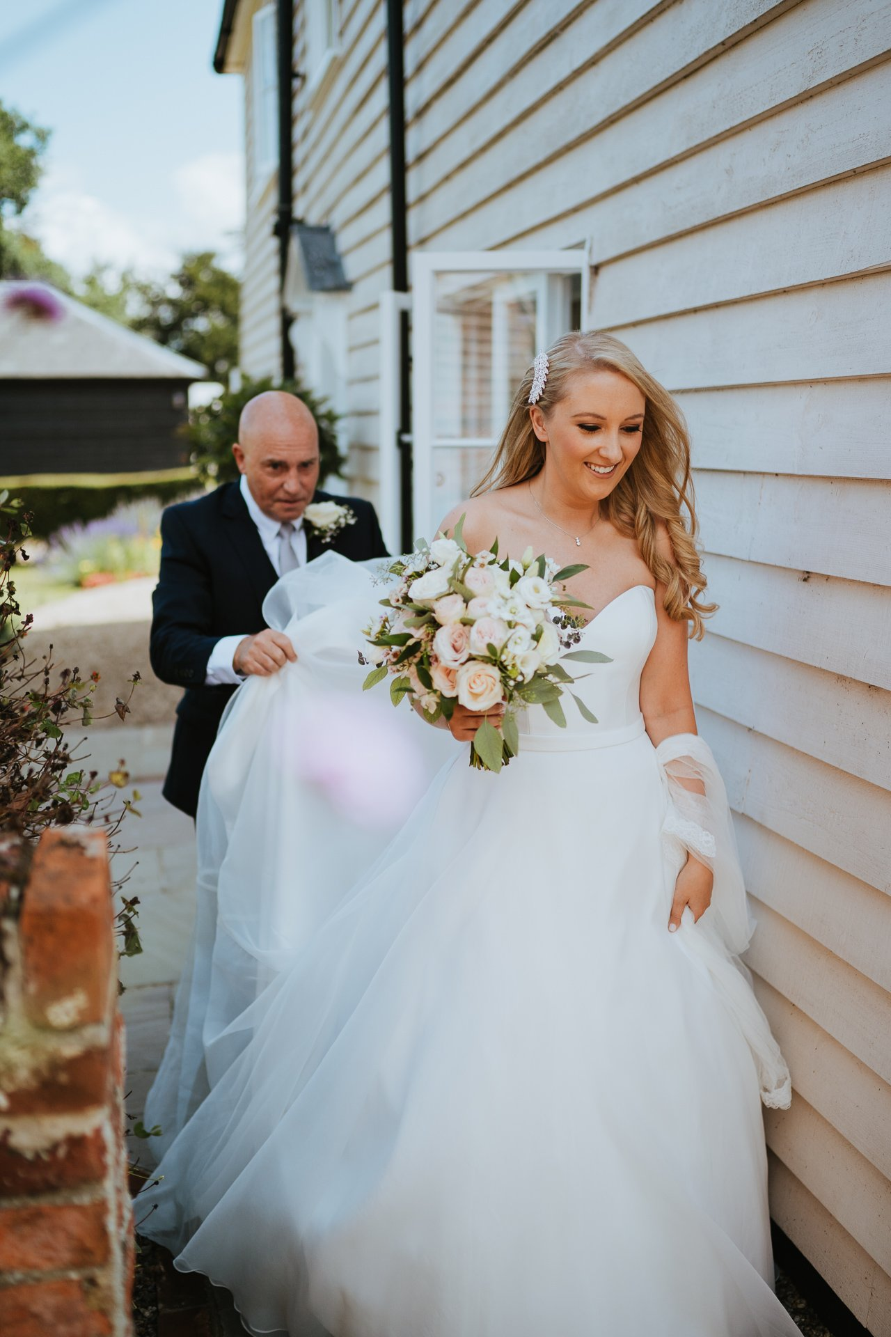Brides father holding her dress for her as she walks to the ceremony