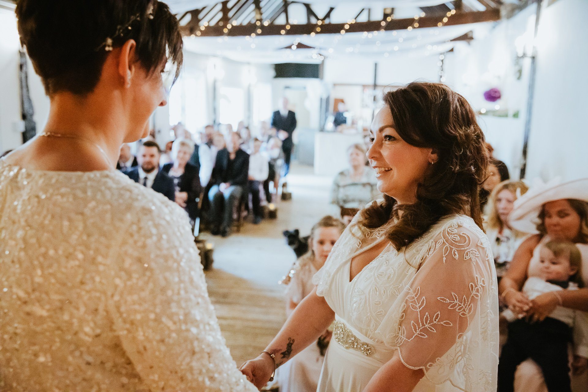 Two brides looking at each other during their wedding ceremony in Kent