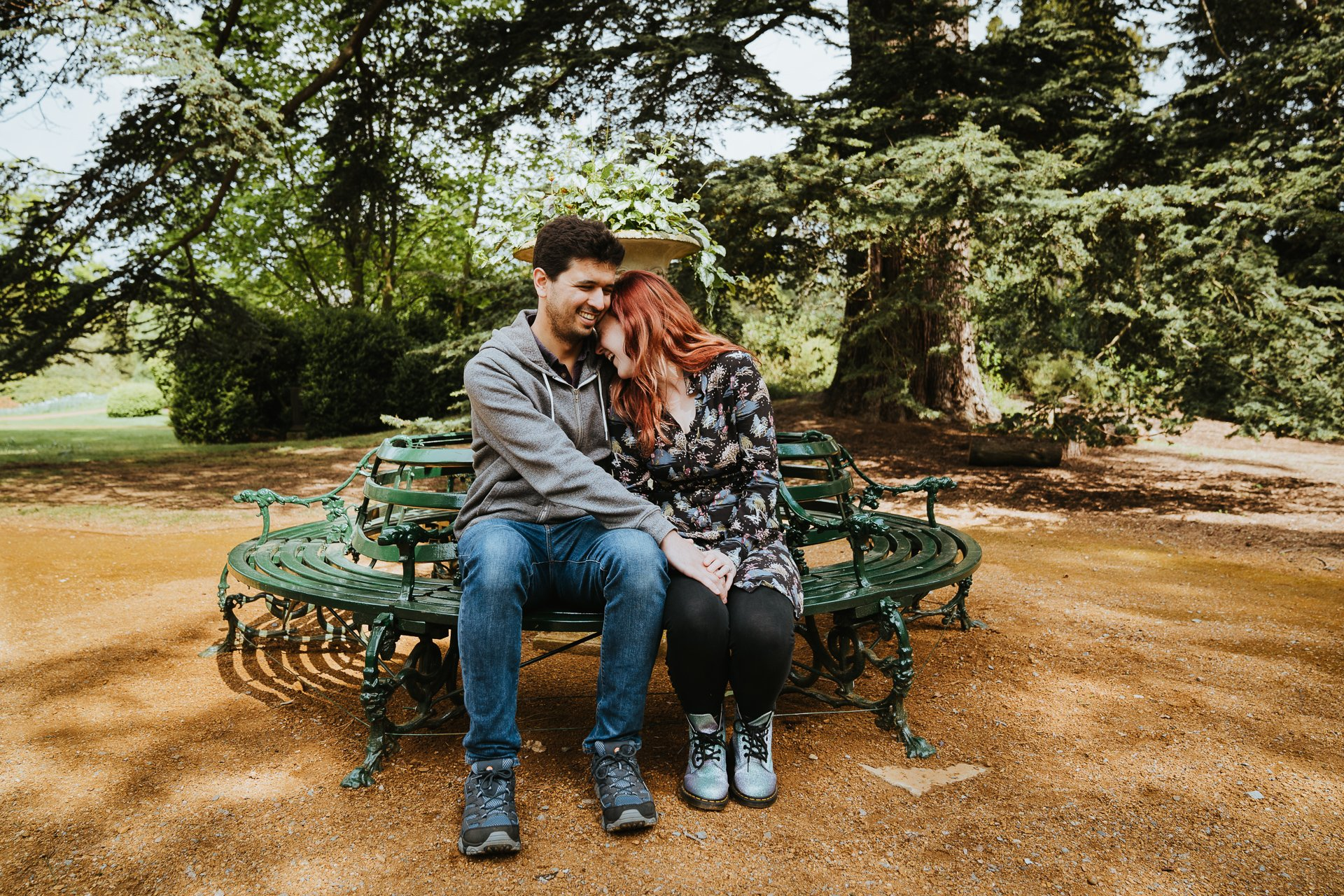 Smiling engaged couple laughing on a bench during pre wedding photography session Kent