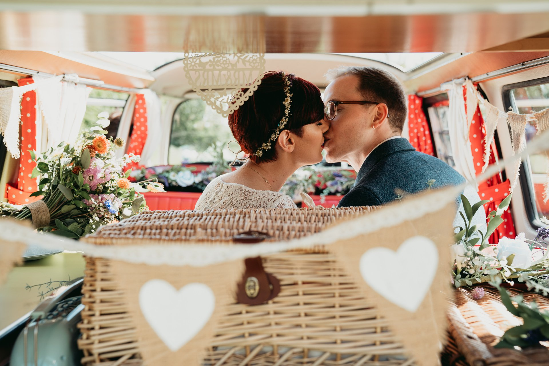 Bride and Groom kissing in the rear of a wedding VW camper van