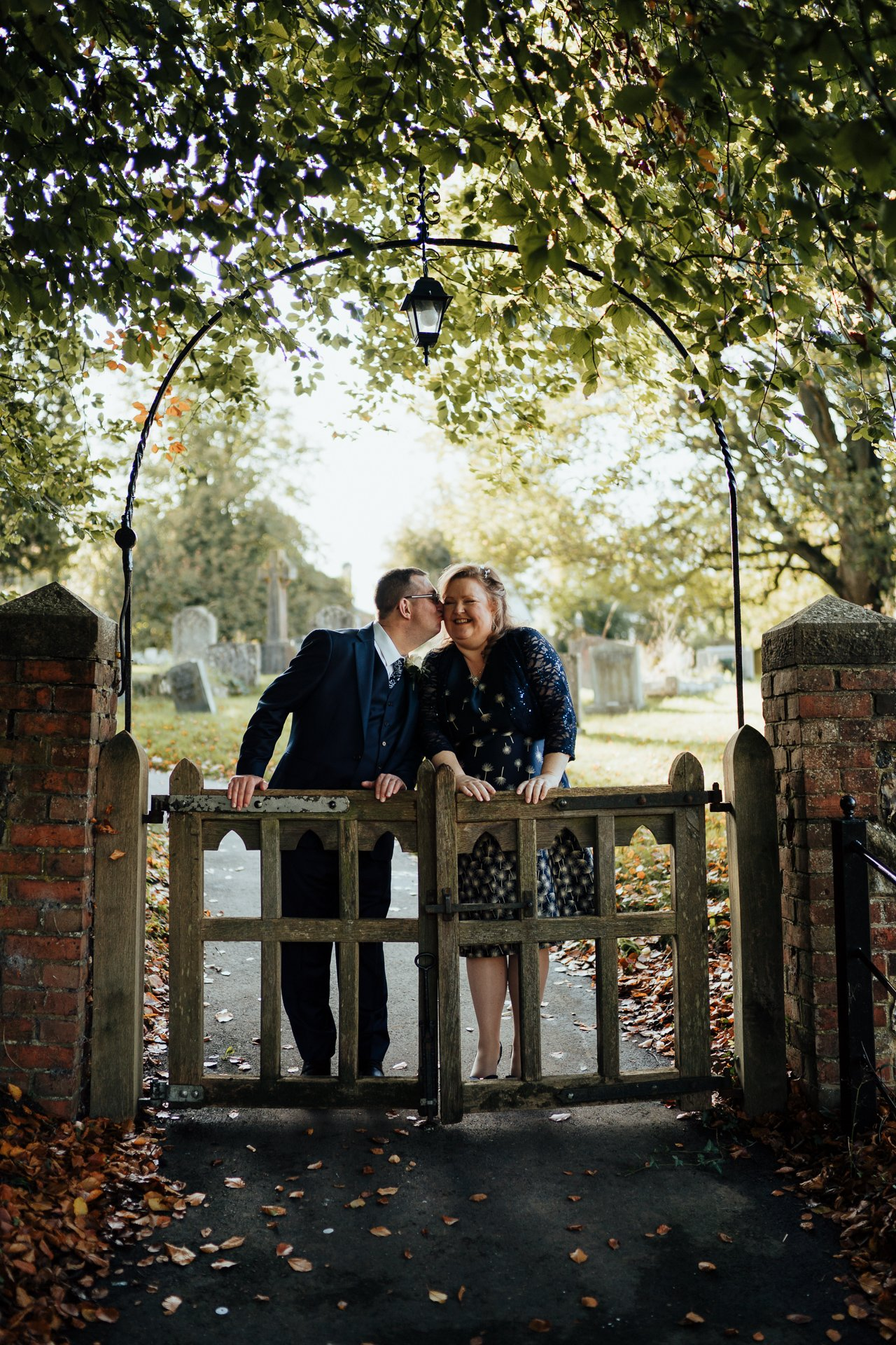 Bride and Groom laughing together and kissing outside their church wedding venue