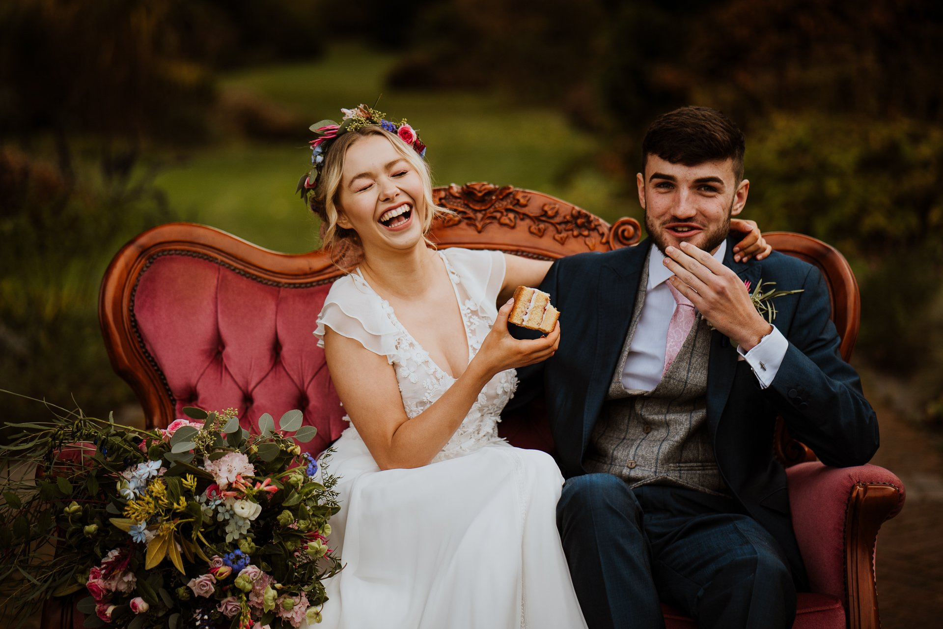 Bride and Groom laughing together eating wedding cake during their wedding day