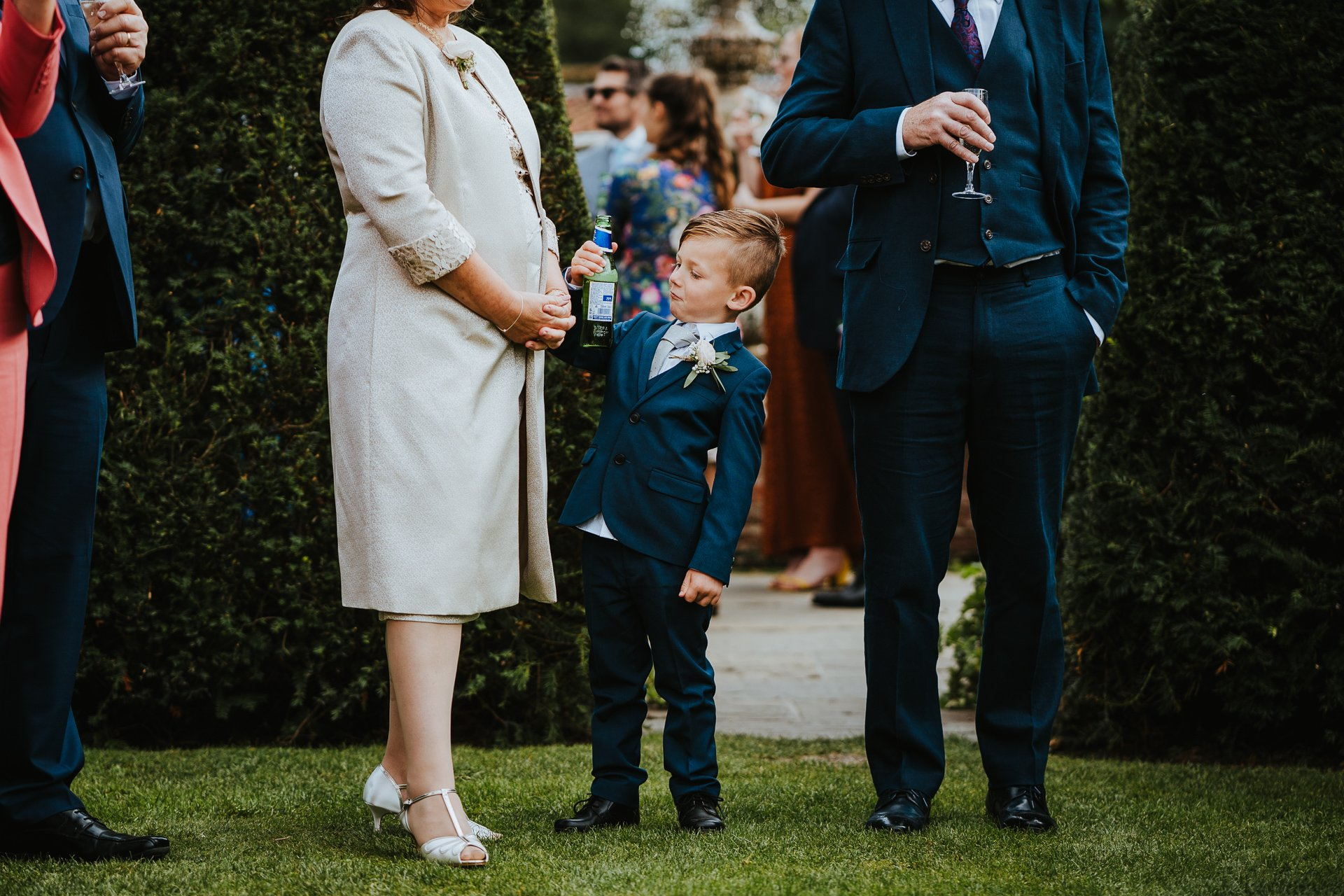 Young boy holding beer bottle and pulling face during wedding ceremony