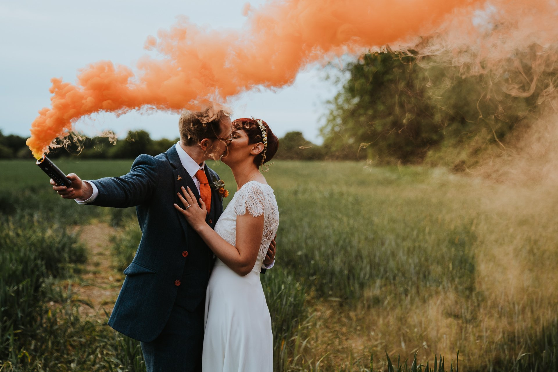Bride and Groom cuddling under smoke bomb