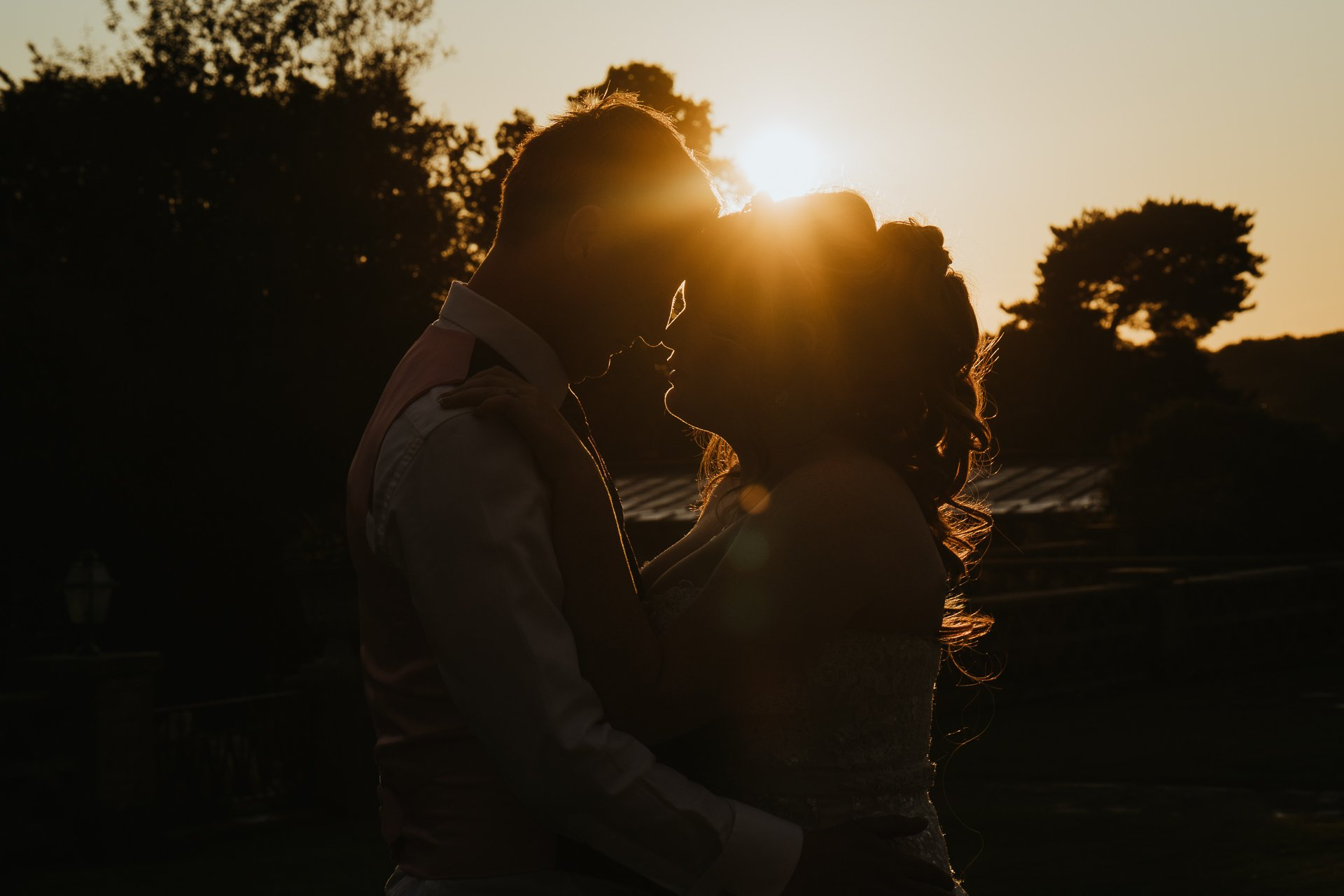 Bride and Groom kissing at sunset during golden hour