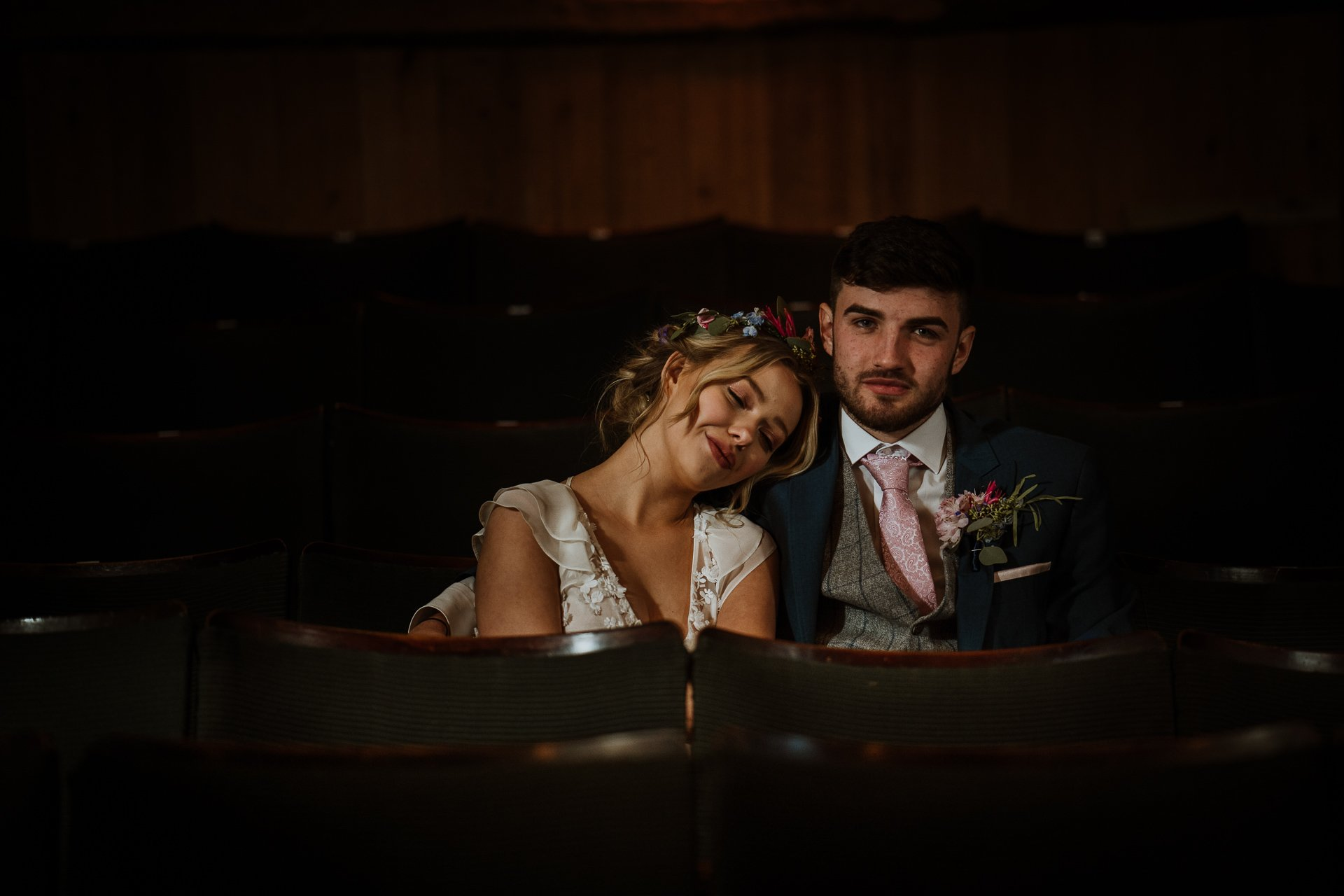 couple hugging in theatre seats after wedding